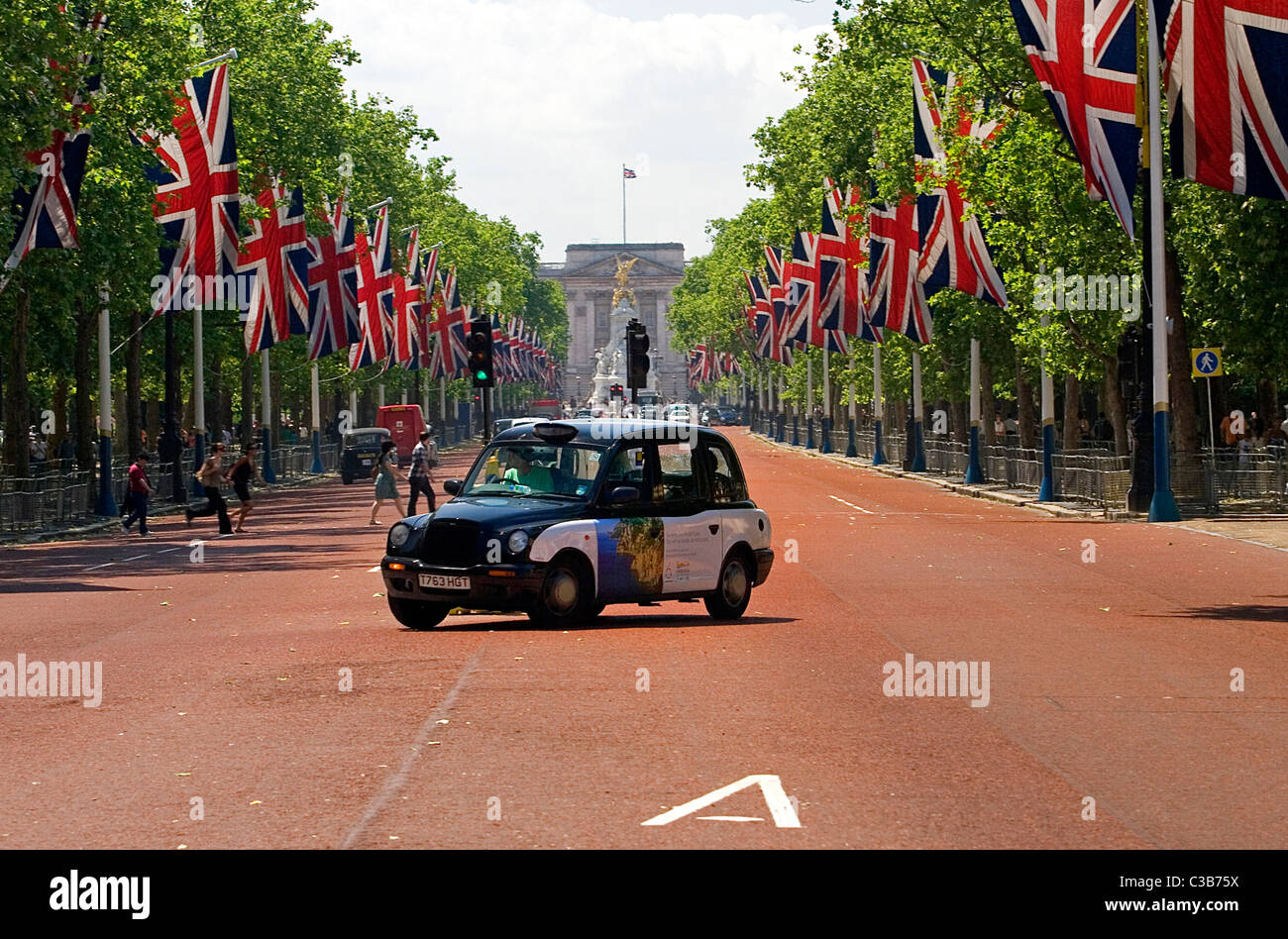 A taxi carrying an advert by Ubiquitous drives along The Mall, London. - Stock Image