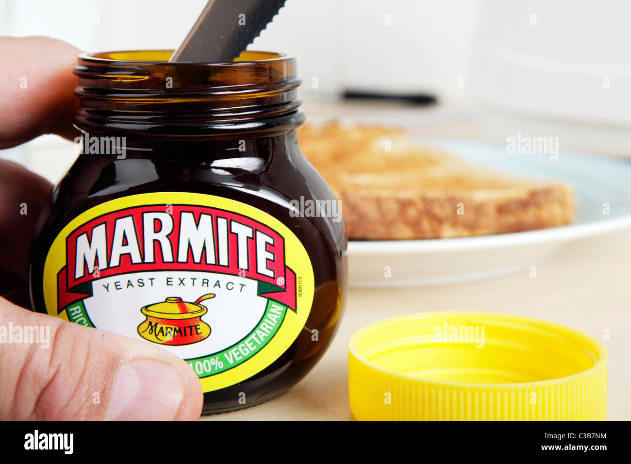 A man getting Marmite out of the jar with a knife. - Stock Image