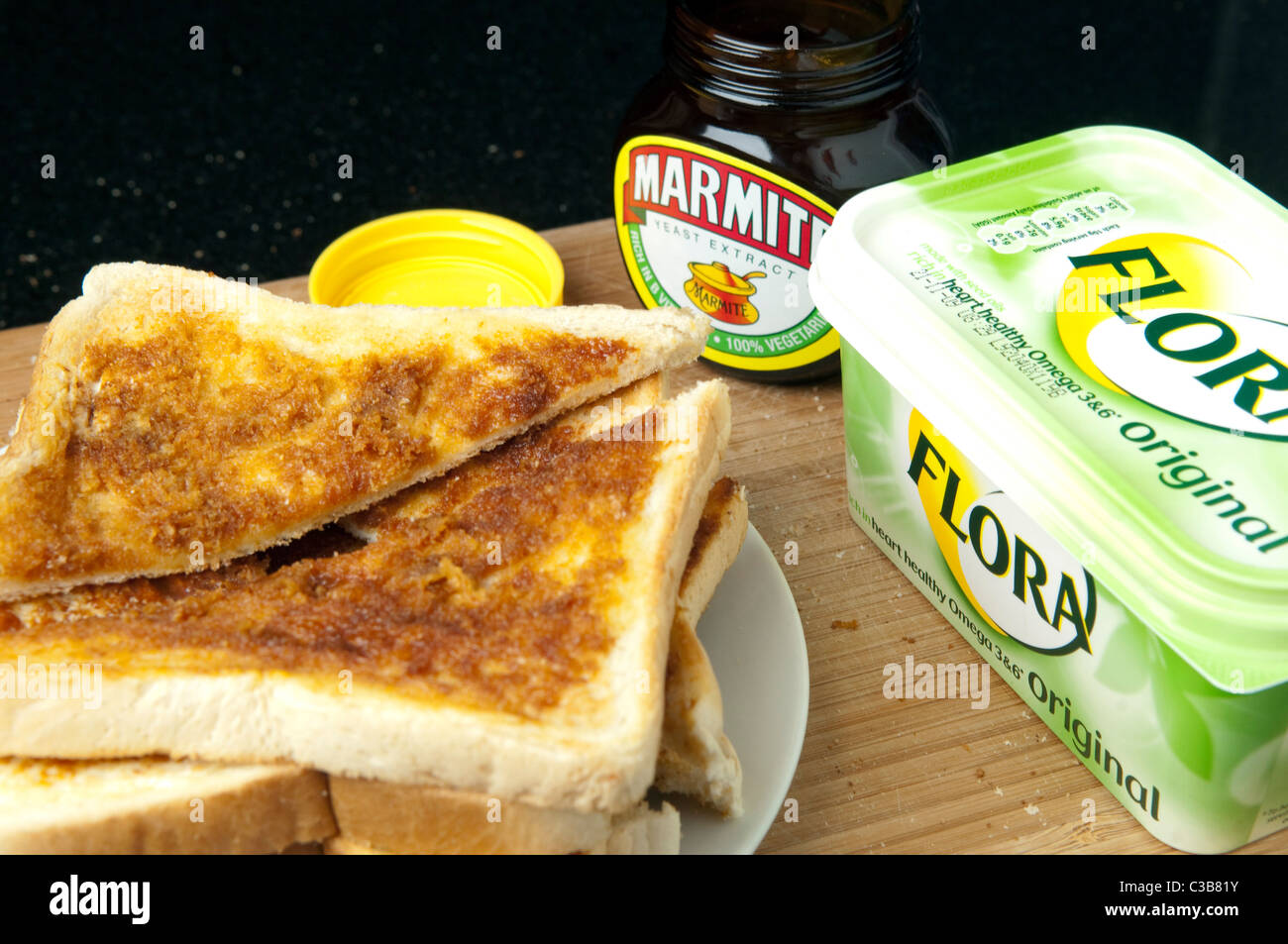 Illustrative image of Marmite and Flora Original spread, two Unilever food products. - Stock Image