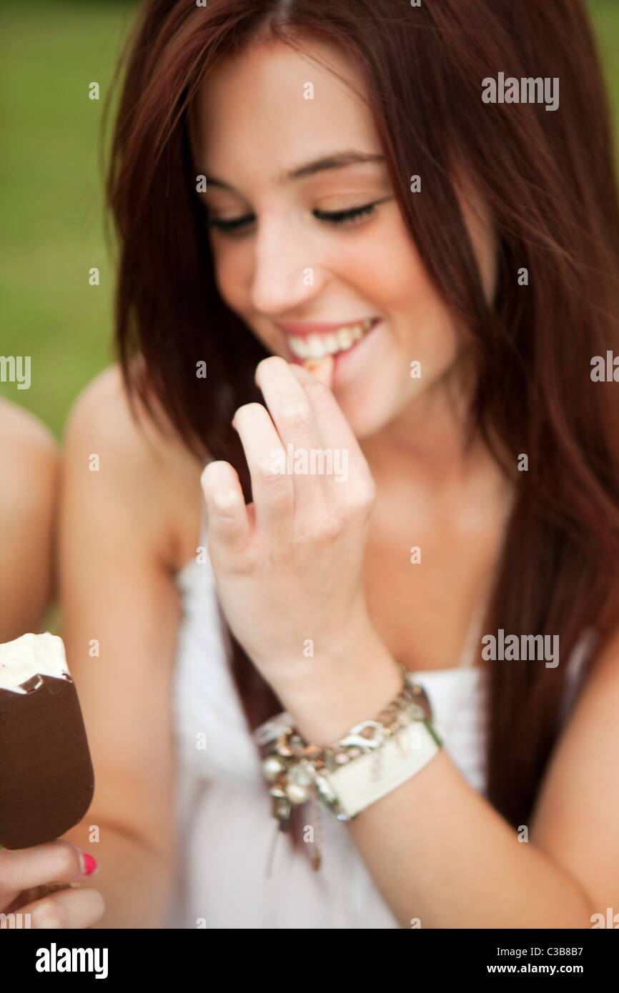 A girl relaxing in the park, enjoying a Magnum ice-cream. - Stock Image