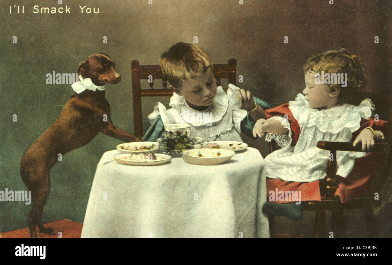 Postcard of cute Edwardian or Victorian children having a tea party with their pet dog. An inscription reads 'I'll - Stock Image