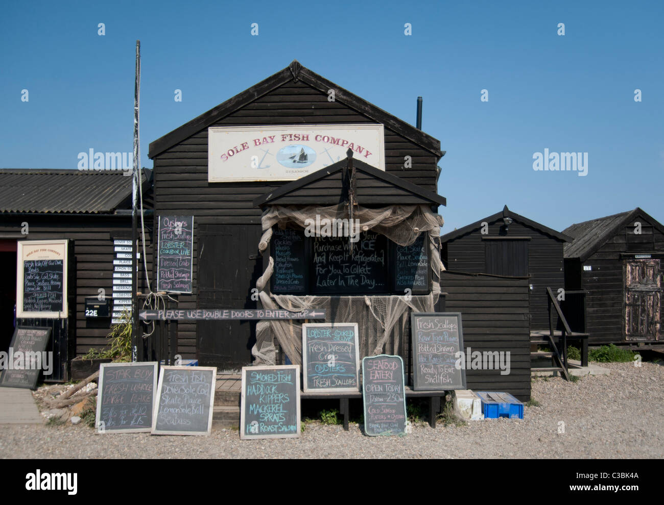 Sole Bay fish Company Fish shop at Southwold Harbour Suffolk England UK. Wooden shed with many signs advertising - Stock Image