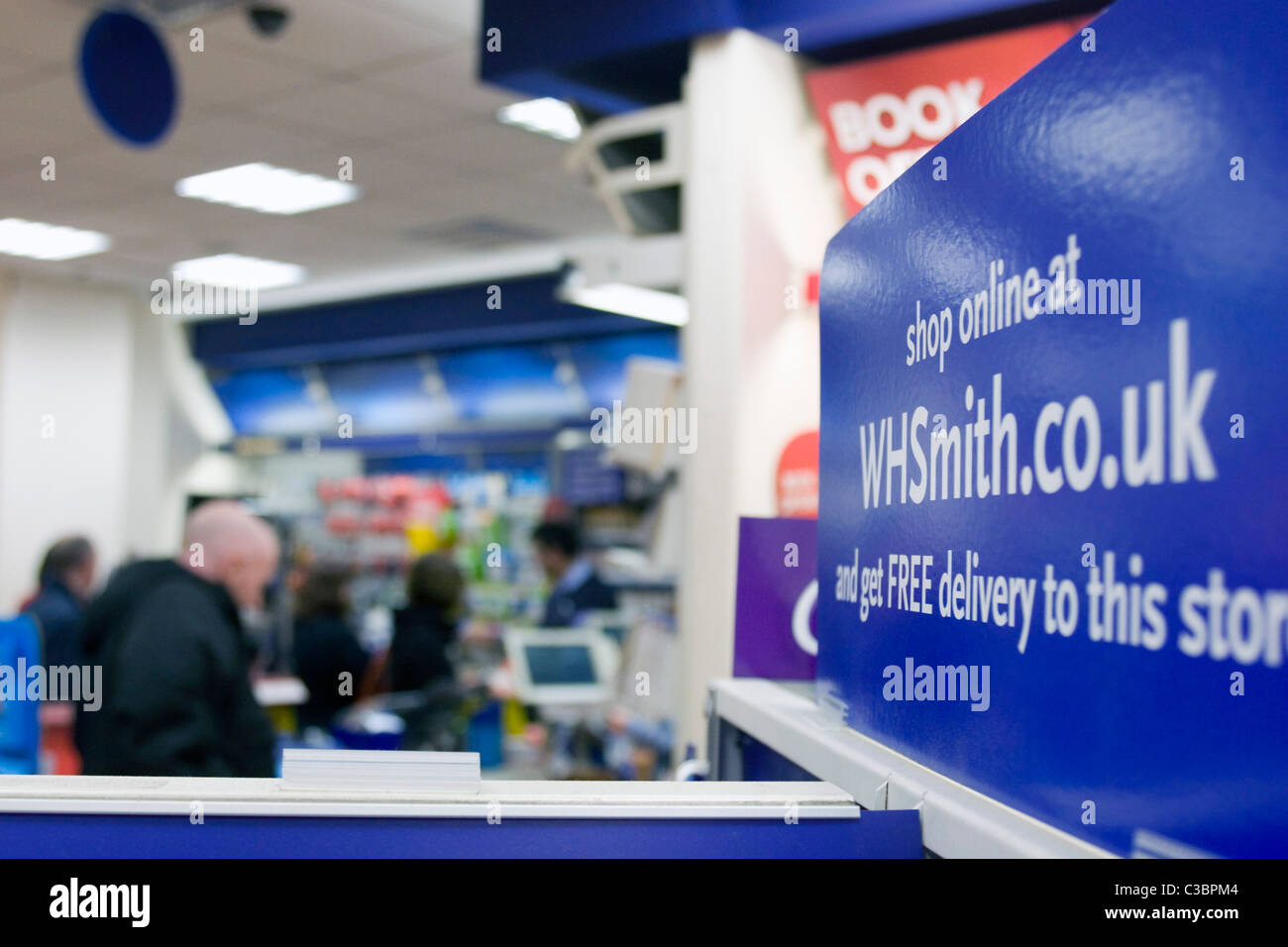 A whsmith.co.uk advert, with customers queuing inside a WH Smith store. - Stock Image