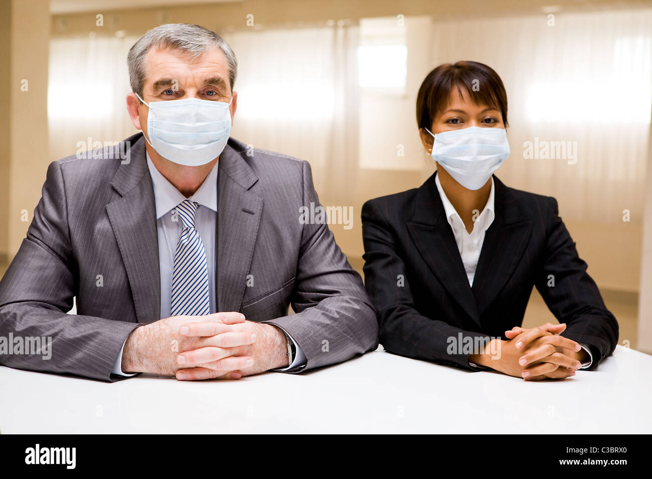 Portrait of two business partners in protective masks looking at camera - Stock Image
