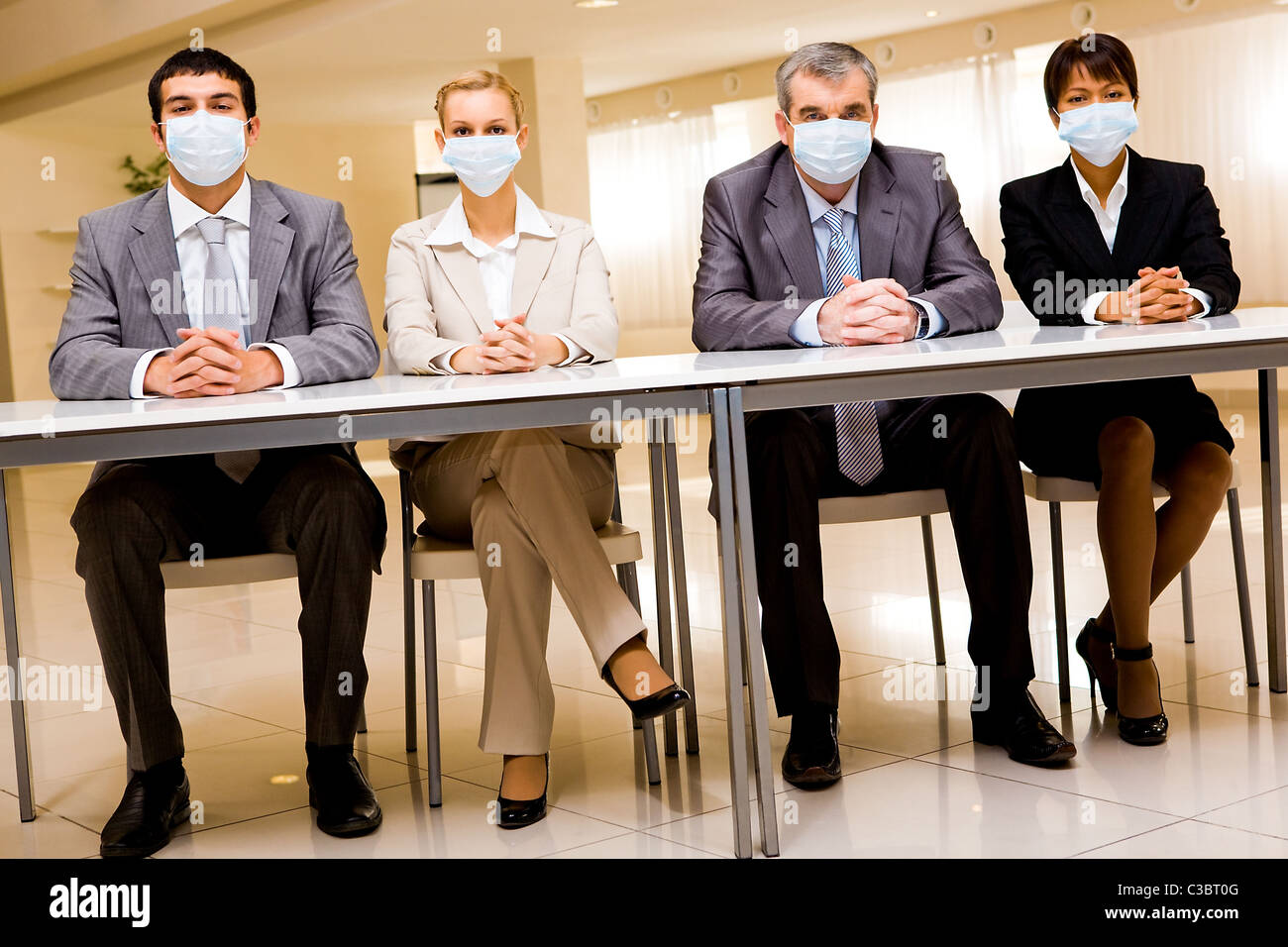 Portrait of group of business partners in protective masks looking at camera - Stock Image