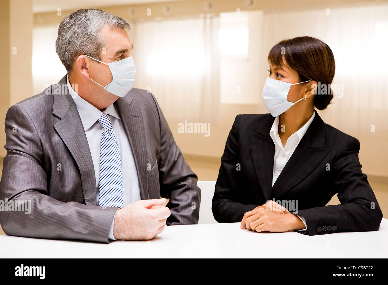 Portrait of two business partners in protective masks looking at each other - Stock Image