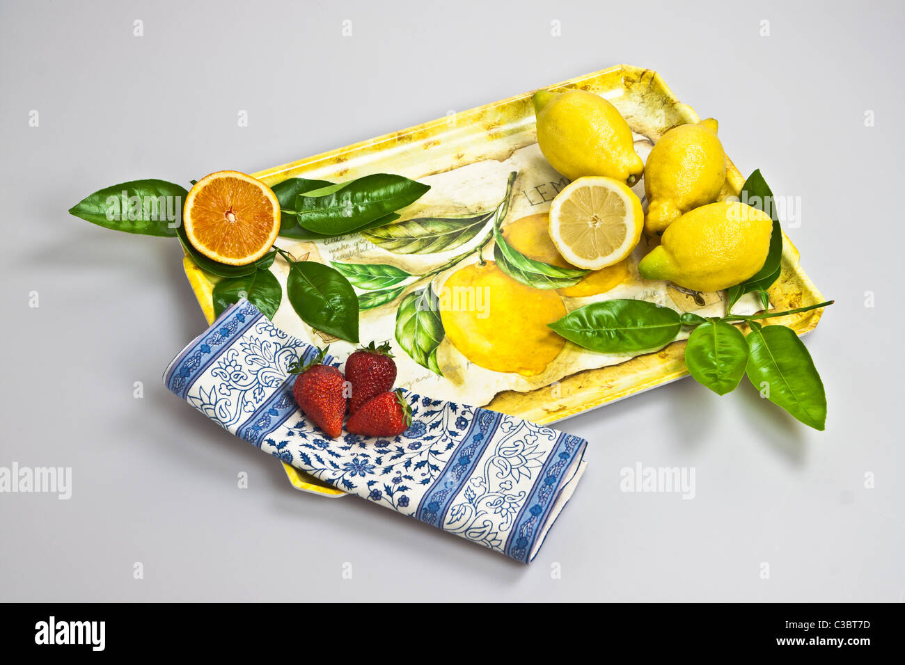 a tray with orange, lemons and strawberries - Stock Image
