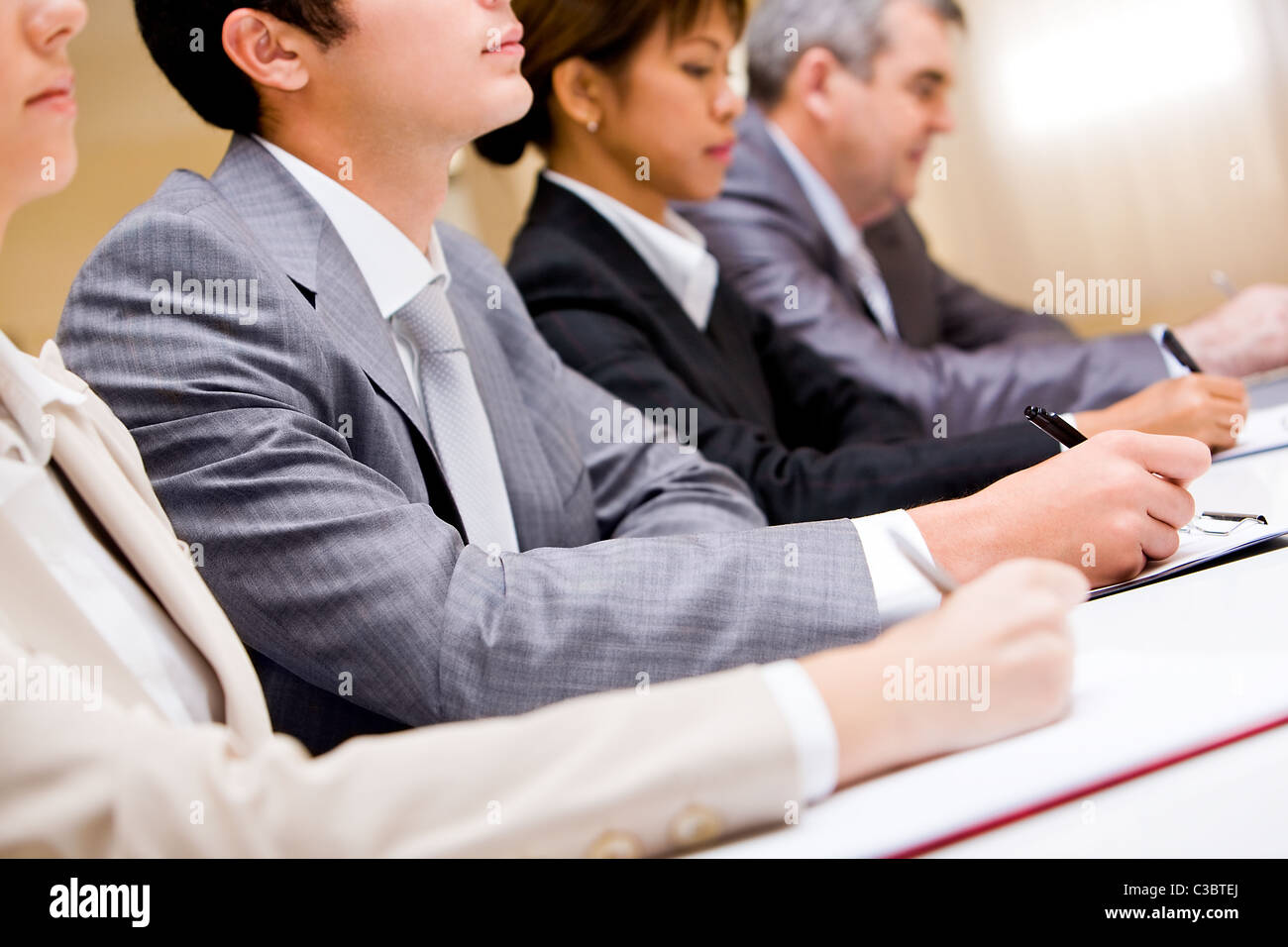 Row of business people making notes during conference - Stock Image