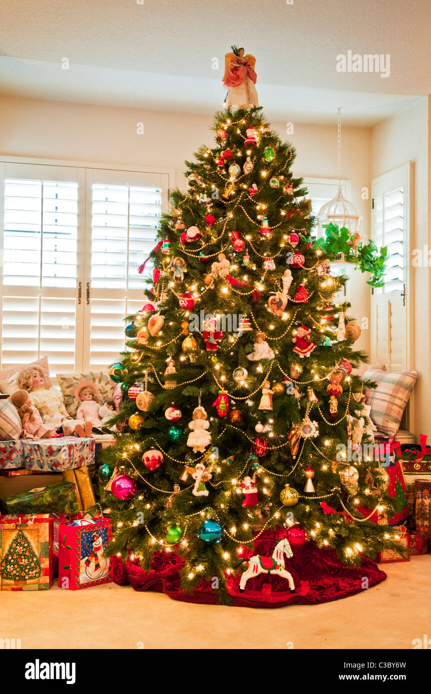 Christmas tree with traditional decorations and dolls in living room of house. - Stock Image
