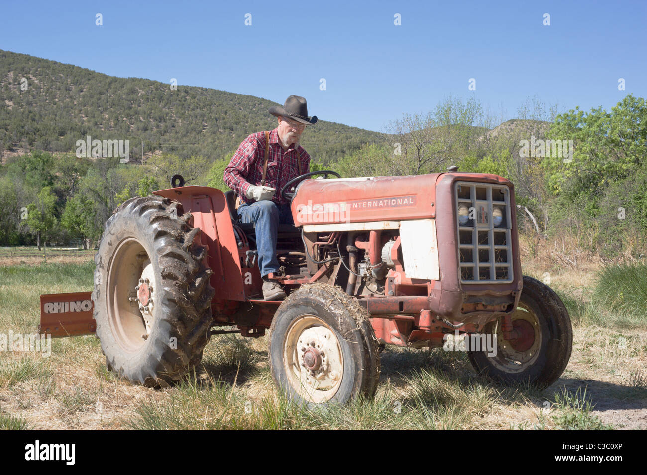 American farmer and rancher prepares the soil for spring planting, in the Hondo Valley, New Mexico. - Stock Image