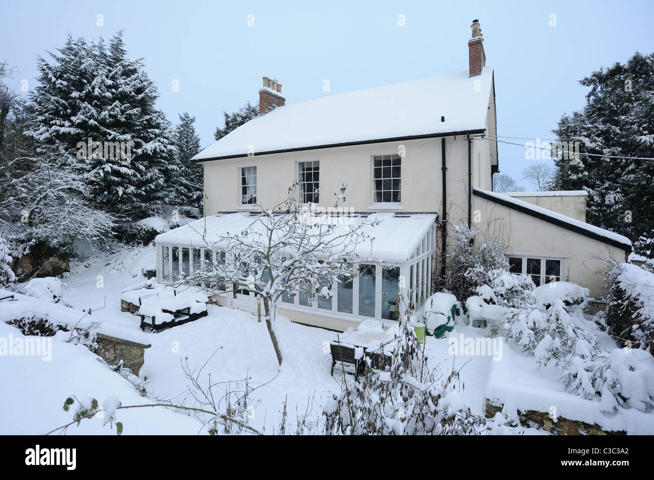 Country house, conservatory and snow covered garden on a cold day morning in East Devon - Stock Image