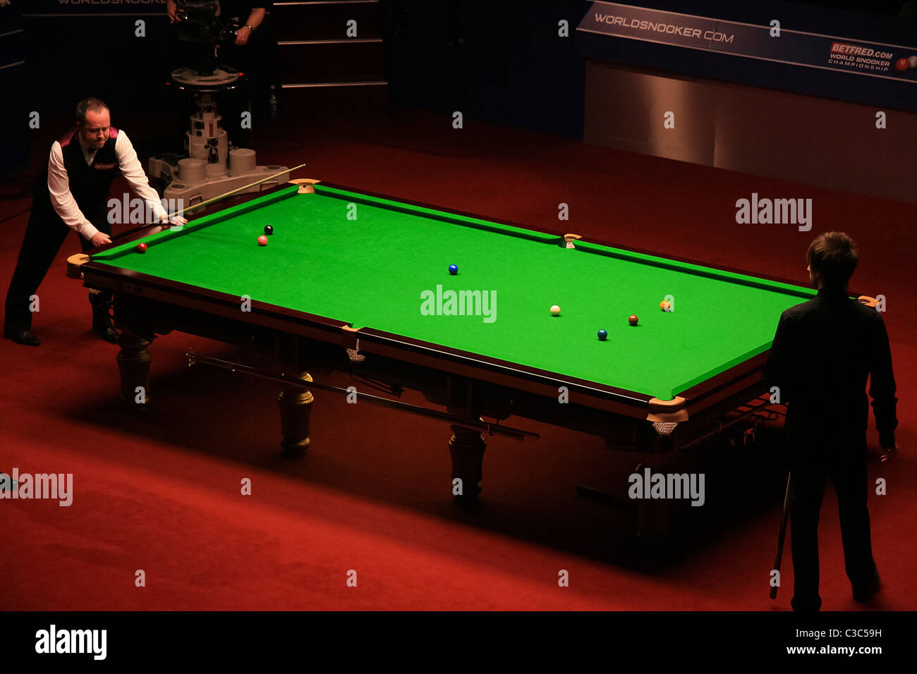 John Higgins in action against Judd Trump at the second session of the World Championship final at the Crucible, - Stock Image