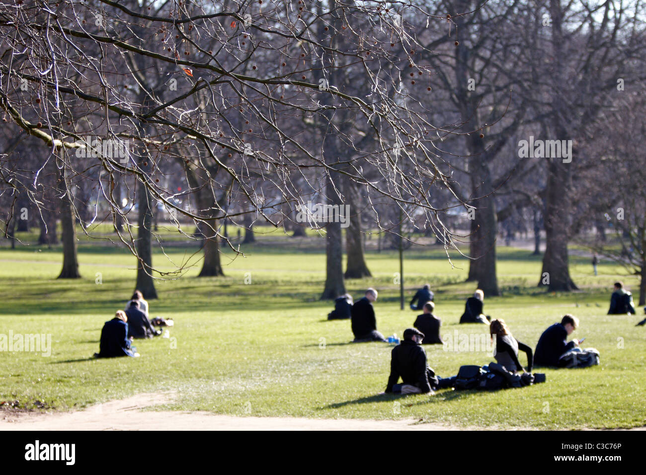 People relax in Green Park London during unseasonal warm February weather - Stock Image