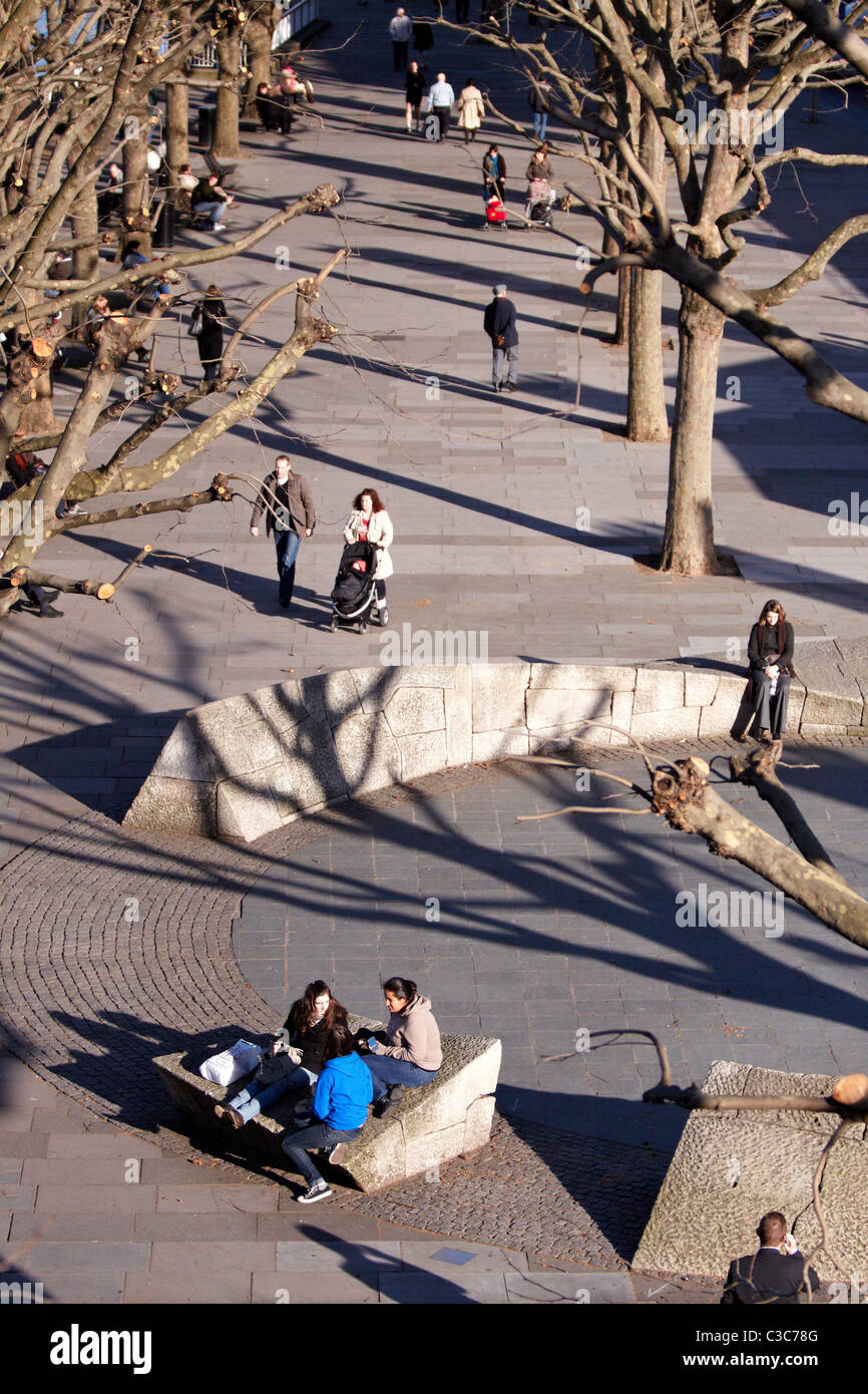 People relax on South Bank, London during unseasonal warm February weather - Stock Image