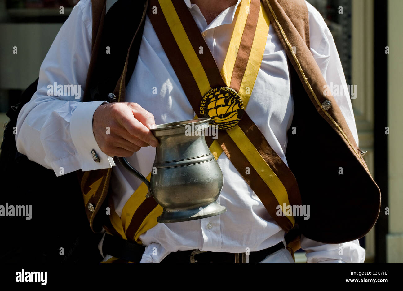 A member of Greenwich Morris Men holding a two pint tankard. - Stock Image
