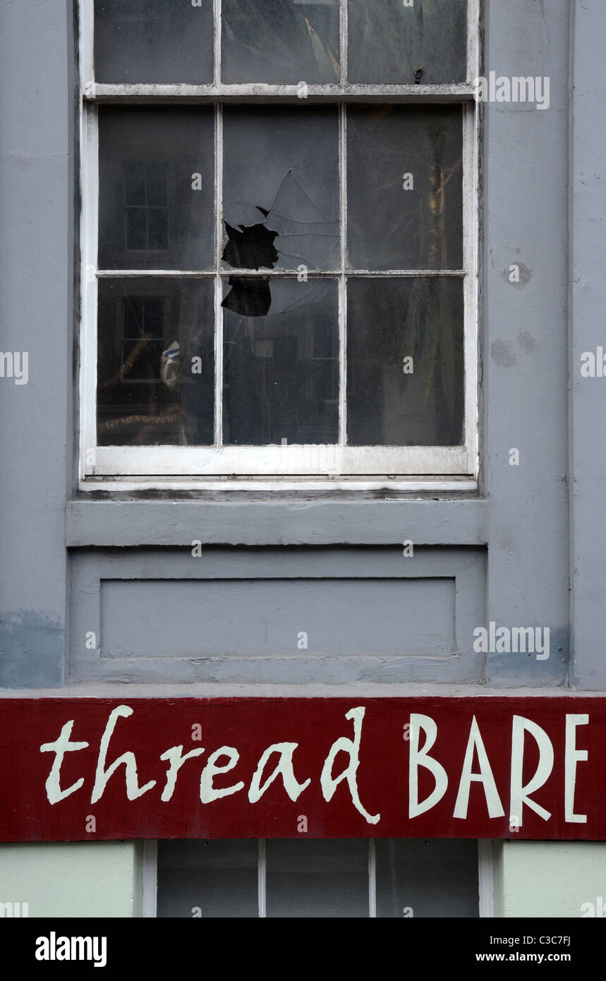 A broken window above the appropriately name 'Thread Bare' dressmaker's shop in Broughton Street, Edinburgh, - Stock Image