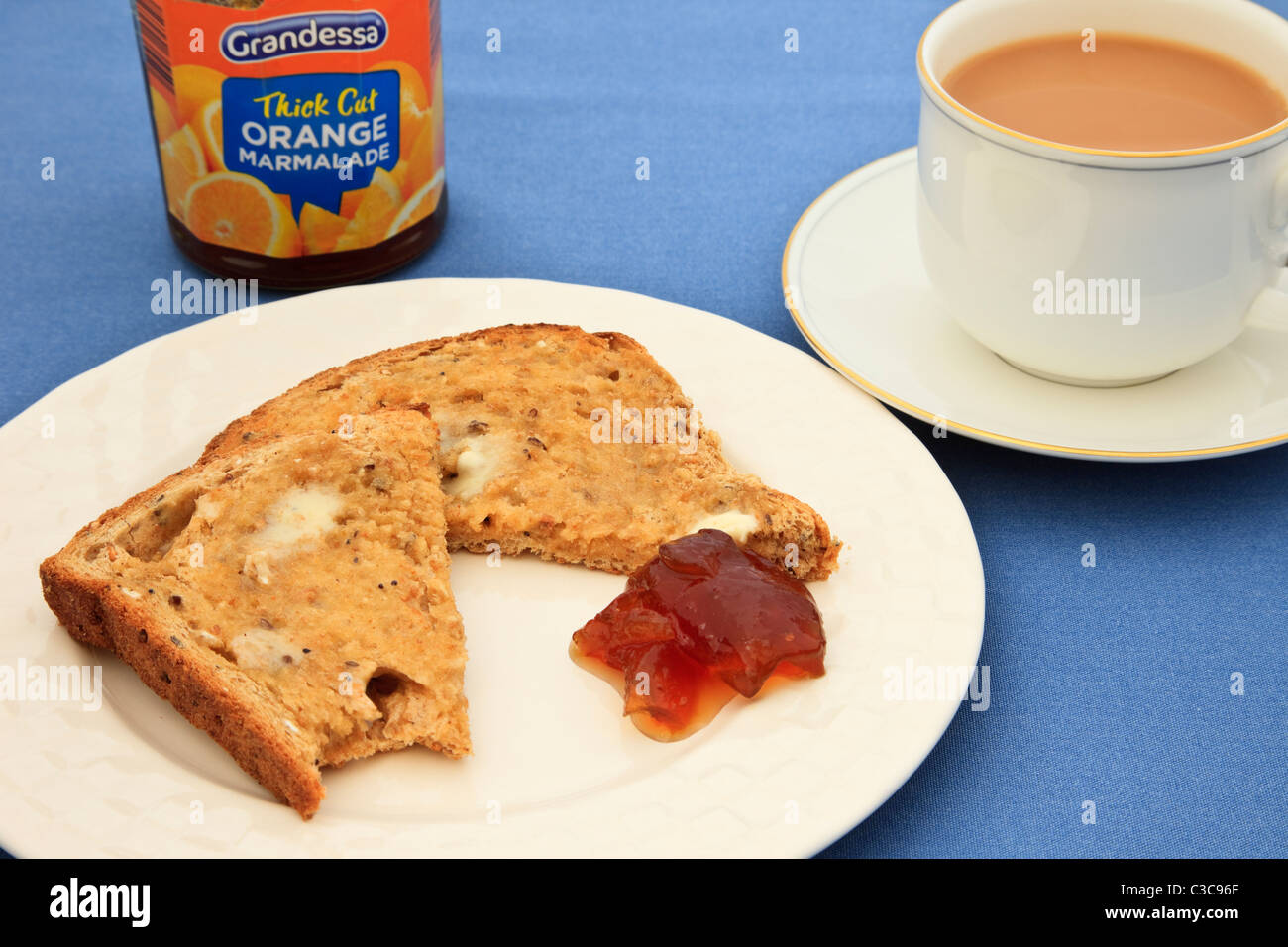 A slice of partly eaten buttered brown bread toast with a jar of marmalade and a cup of tea on a saucer on a blue - Stock Image
