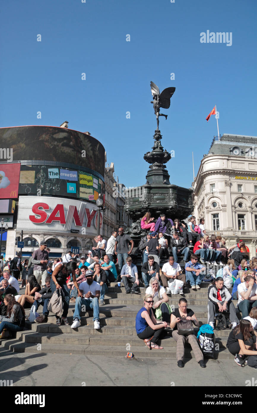 Crowds of tourist enjoying the sun under the statue of Anteros (it is NOT Eros) in Piccadilly Circus, London, UK. - Stock Image