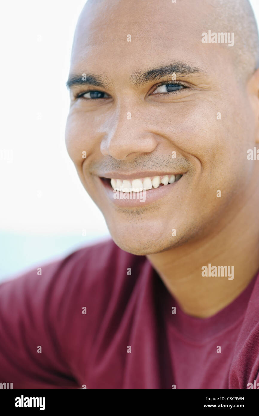 portrait of young hispanic guy with shaved head looking at camera near the sea. Vertical shape, head and shoulders - Stock Image