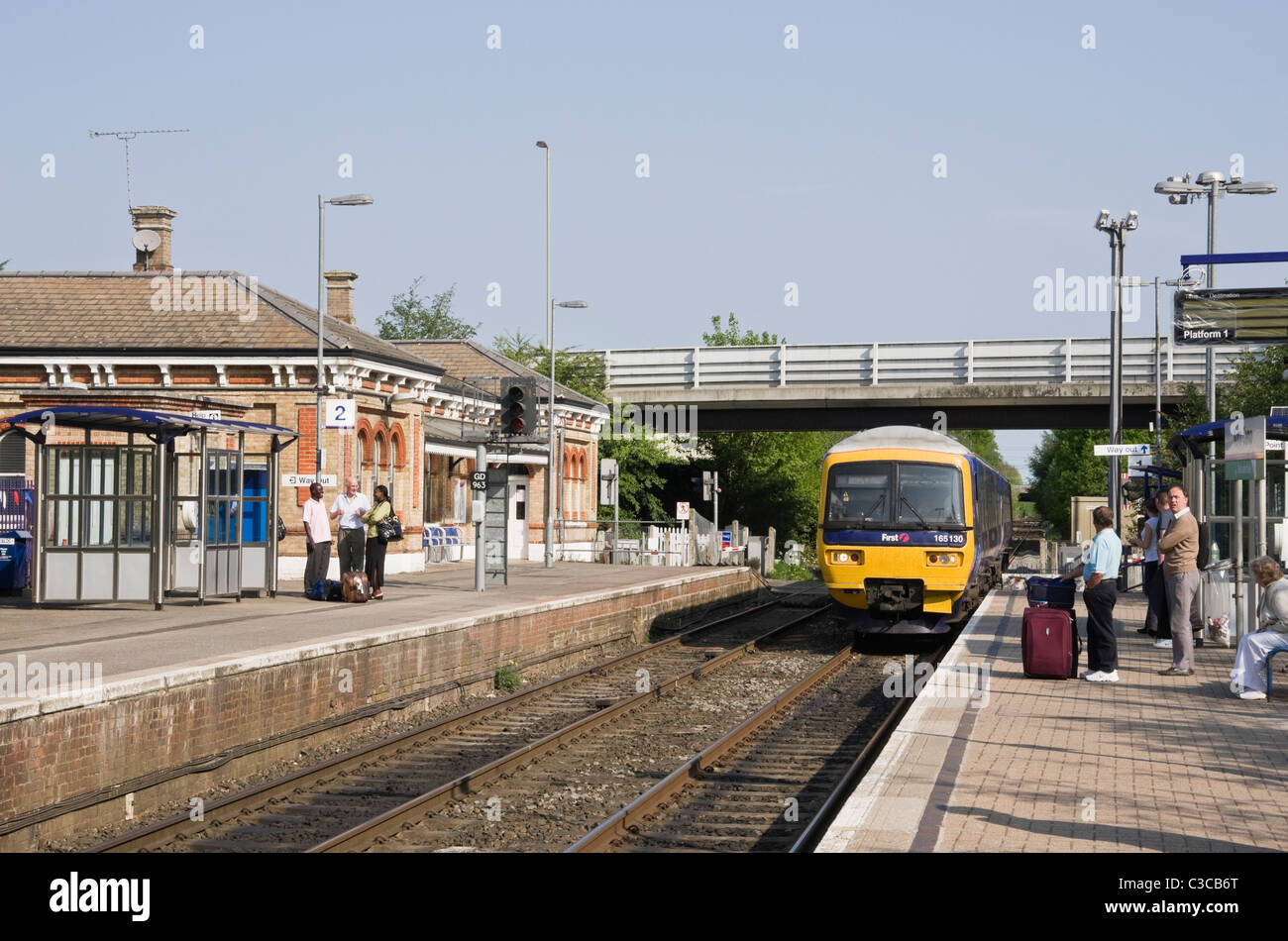 North Camp, Hampshire, England, UK. First Great Western train approaching railway station with passengers waiting - Stock Image