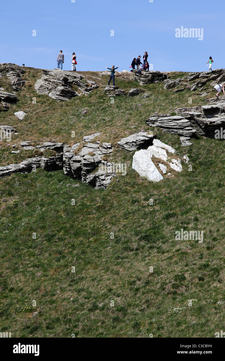 Tourists looking at the scenery on top of the cliffs at Tintagel Cornwall England UK English Heritage - Stock Image