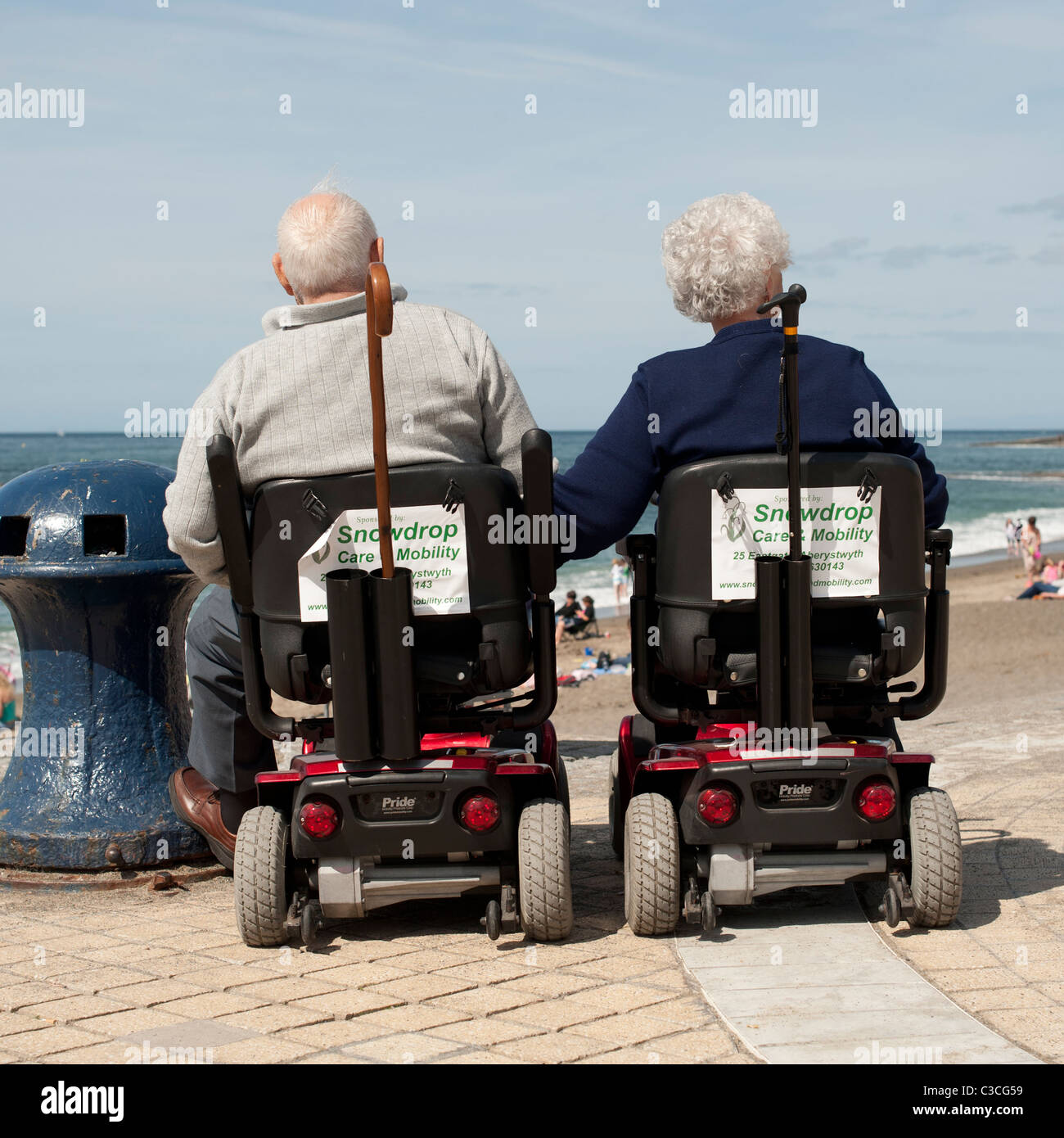 Rear view of an elderly disabled couple husband and wife at the seaside sitting in powered mobility scooters, Aberystwyth - Stock Image