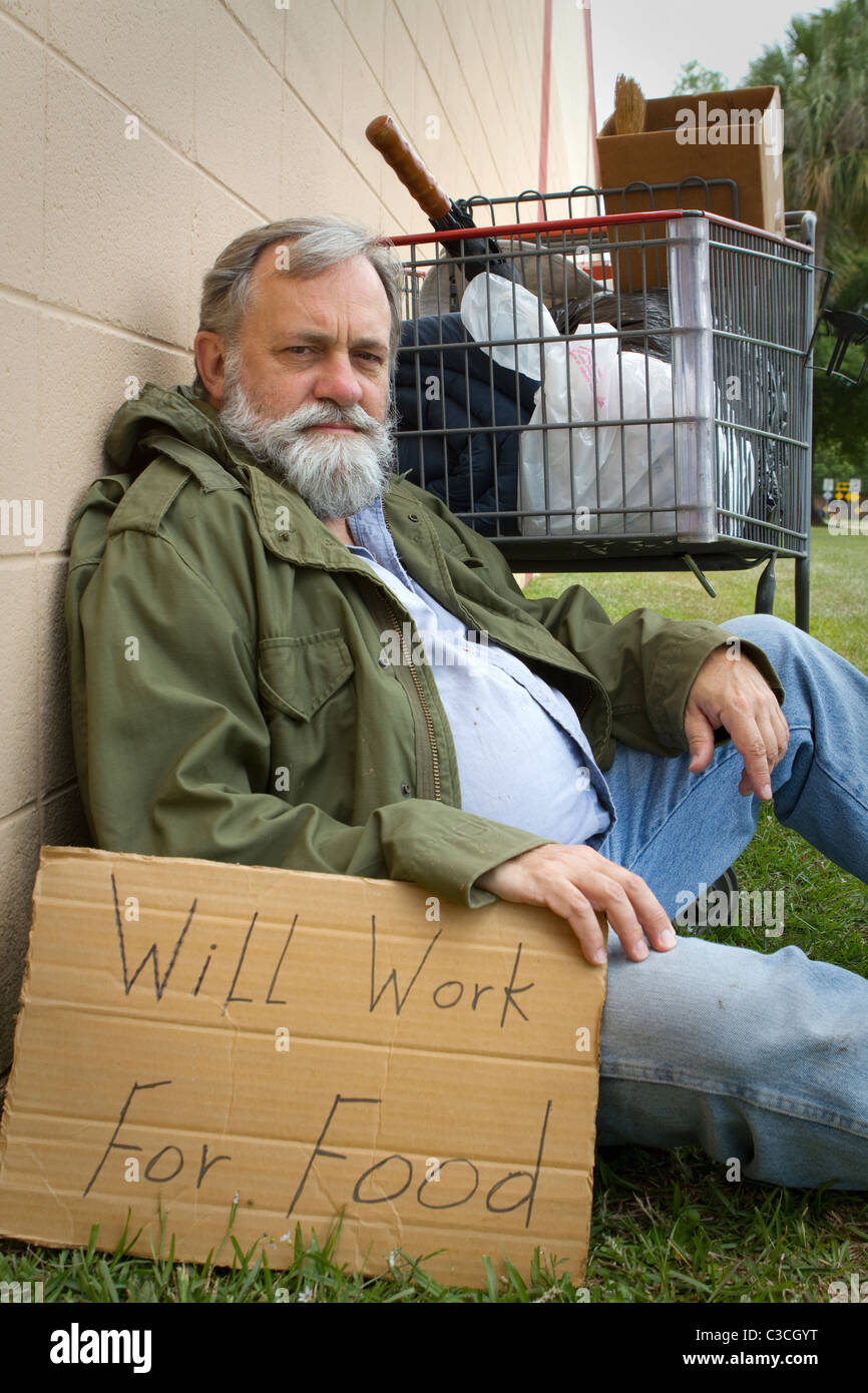 Homeless man rests leaning against a wall hold a sign with his possessions in a grocery cart. - Stock Image
