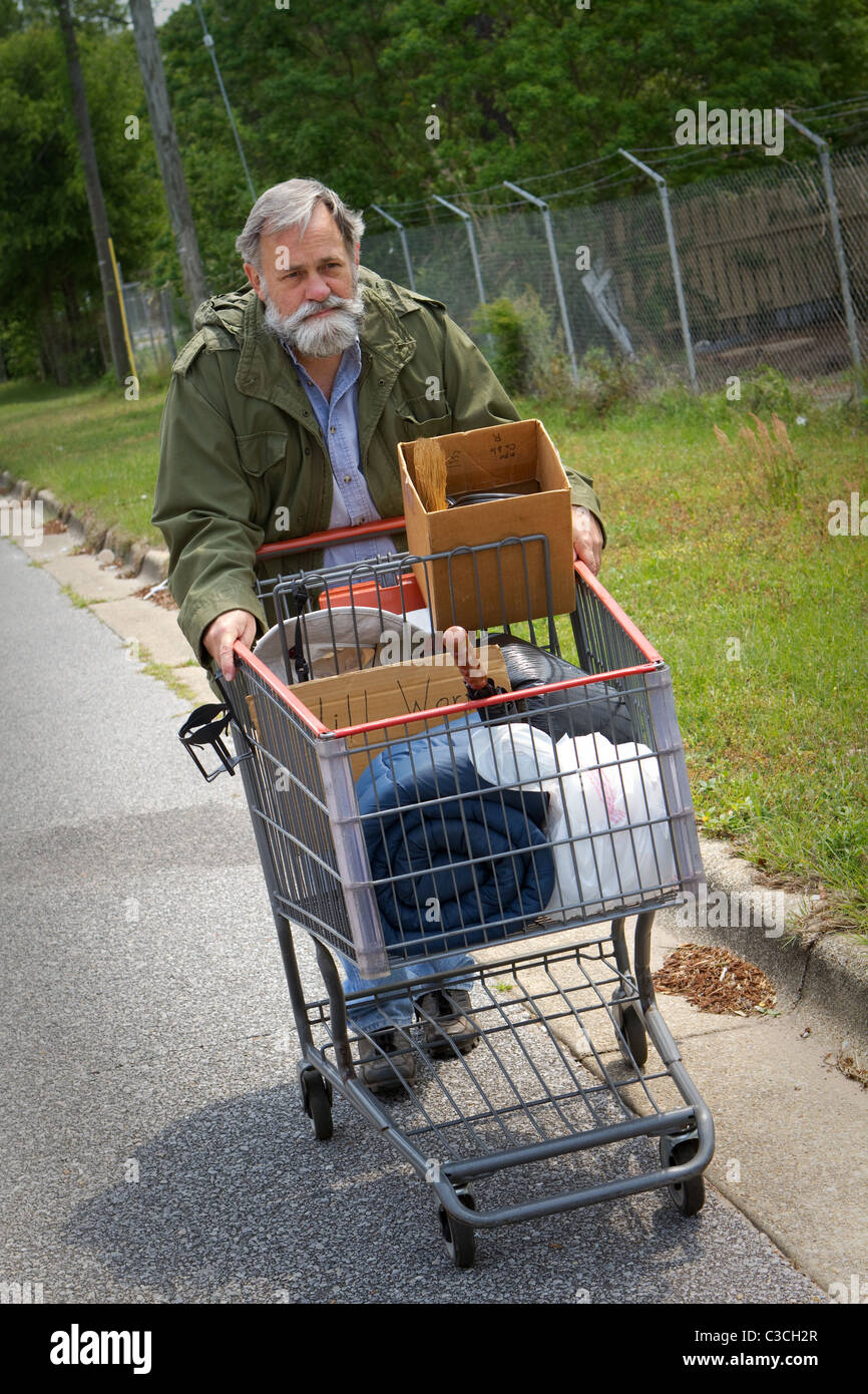 Homeless Vietnam veteran pushes a shopping cart containing his possessions down the side of the street. - Stock Image