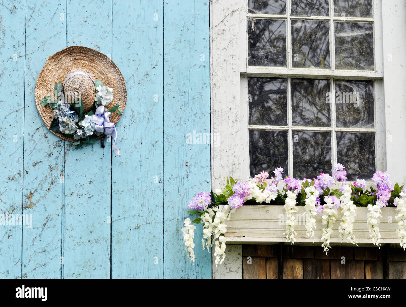 Picturesque Cape Cod barn with flowering window box and decorated straw hat on door. USA - Stock Image