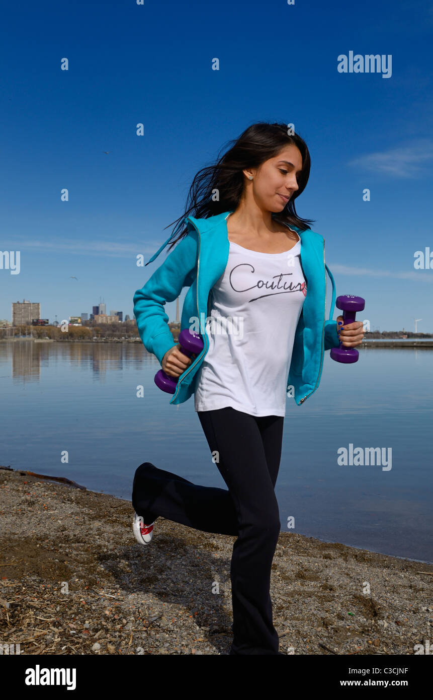 East Indian Teenage girl running along the waterfront of Lake Ontario in Toronto with hand weights against blue - Stock Image
