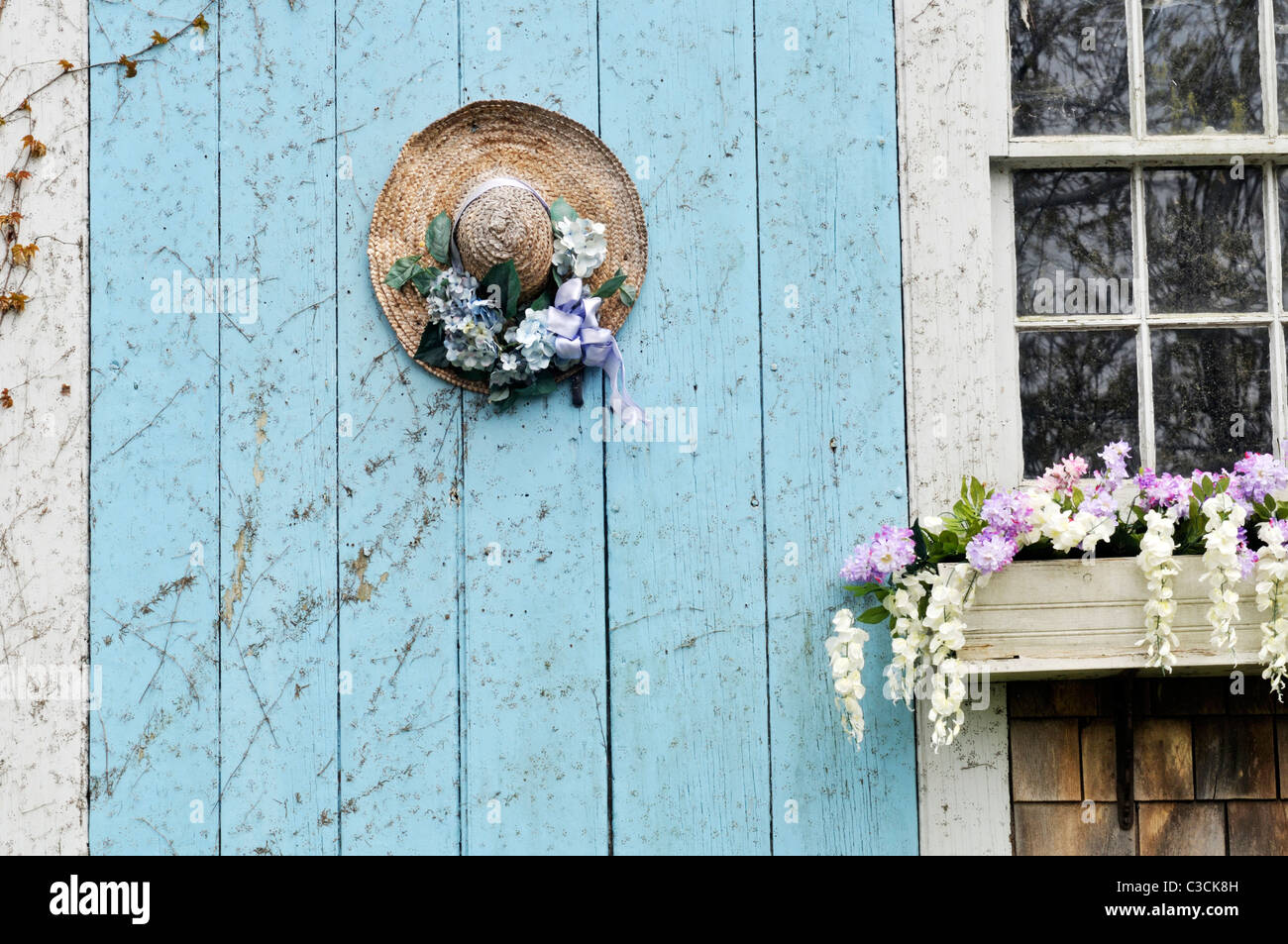 Closeup of picturesque Cape Cod barn door with flowering window box and decorated straw hat on door. USA - Stock Image