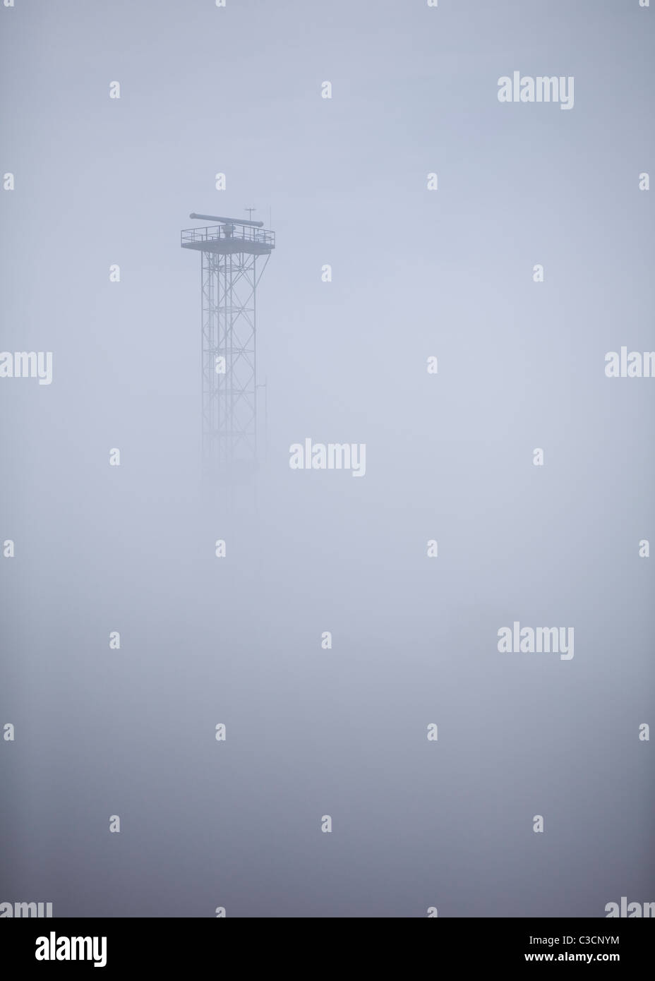Radar antenna tower in heavy fog - Stock Image