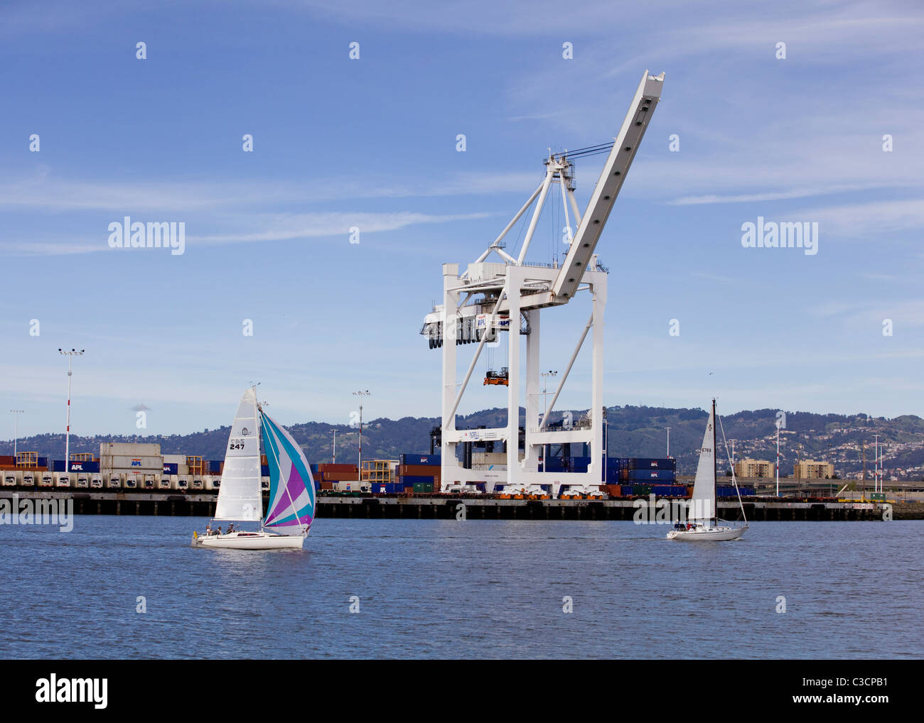 Sail boats and gantry cranes - Port of Oakland, California USA - Stock Image