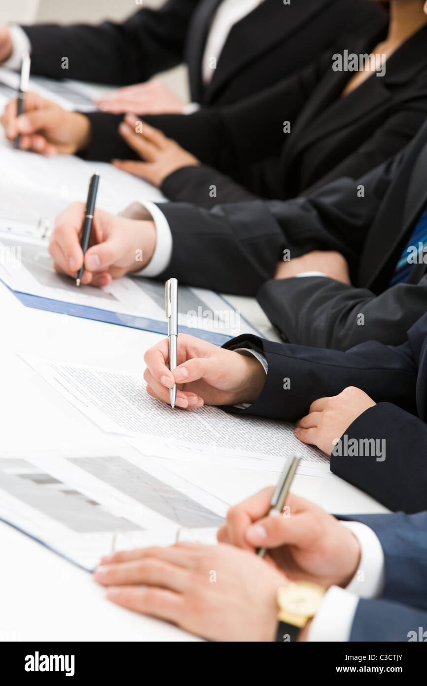 Image of row of people hands writing on papers at seminar - Stock Image