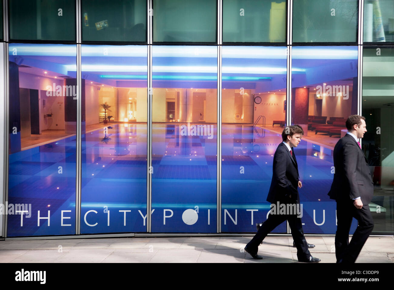 City workers walk past The Citypoint Club a fitness and spa center based in the City of London. - Stock Image