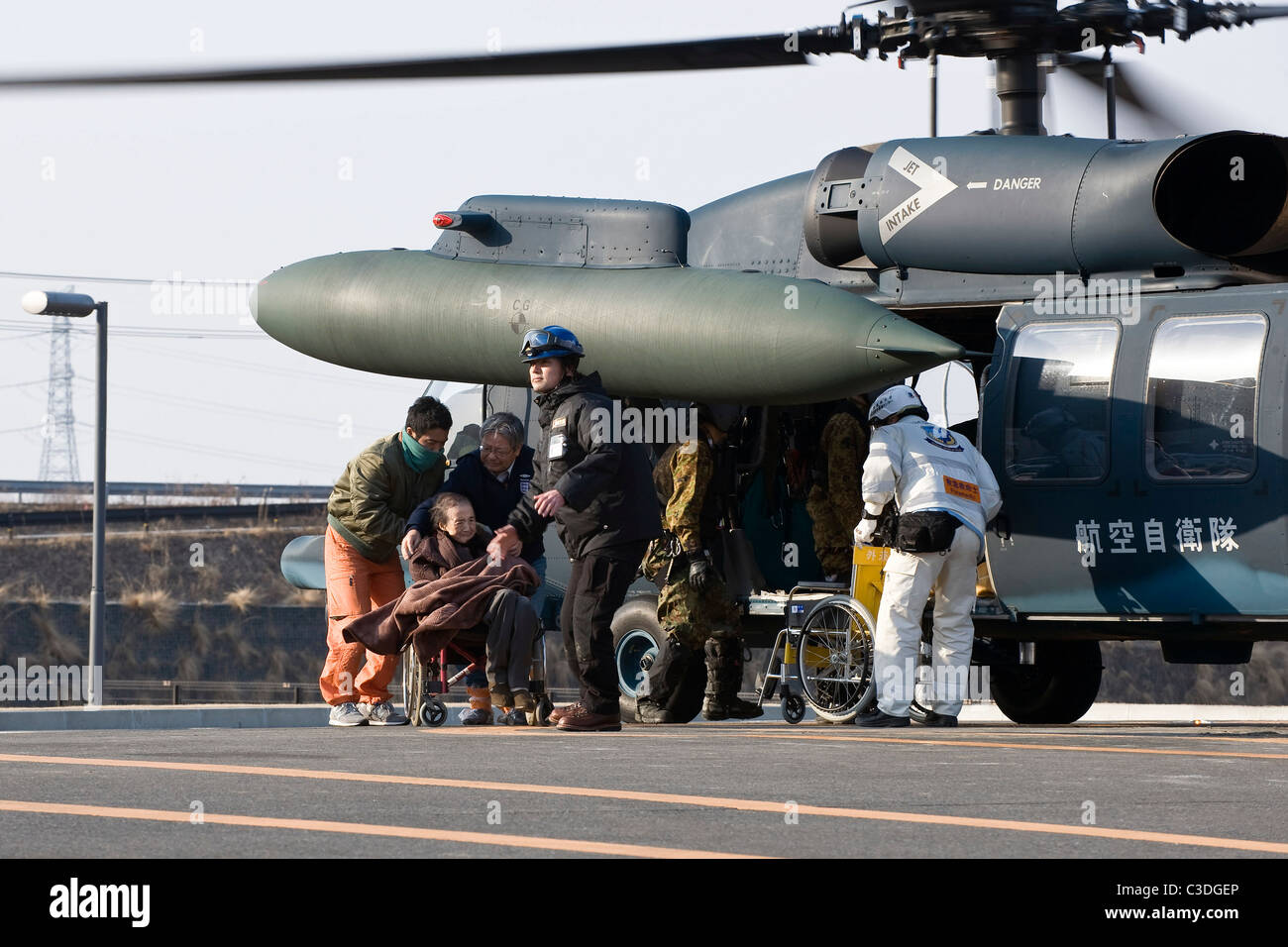 An elderly woman is helped off a helicopter after being evacuated from her home to a hospital in Ishinomaki, Japan - Stock Image