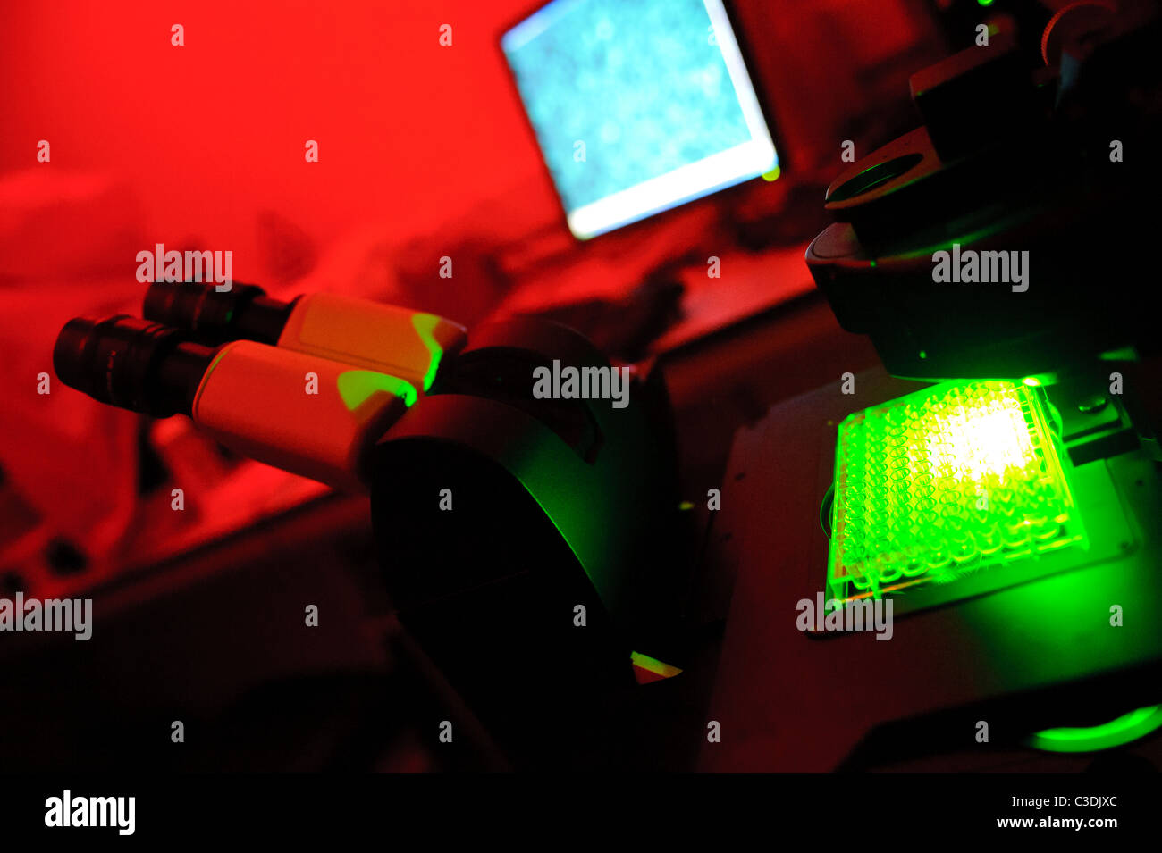 microscope in darkroom lit bright red with computer screen in background and green and blue lights test tubes - Stock Image
