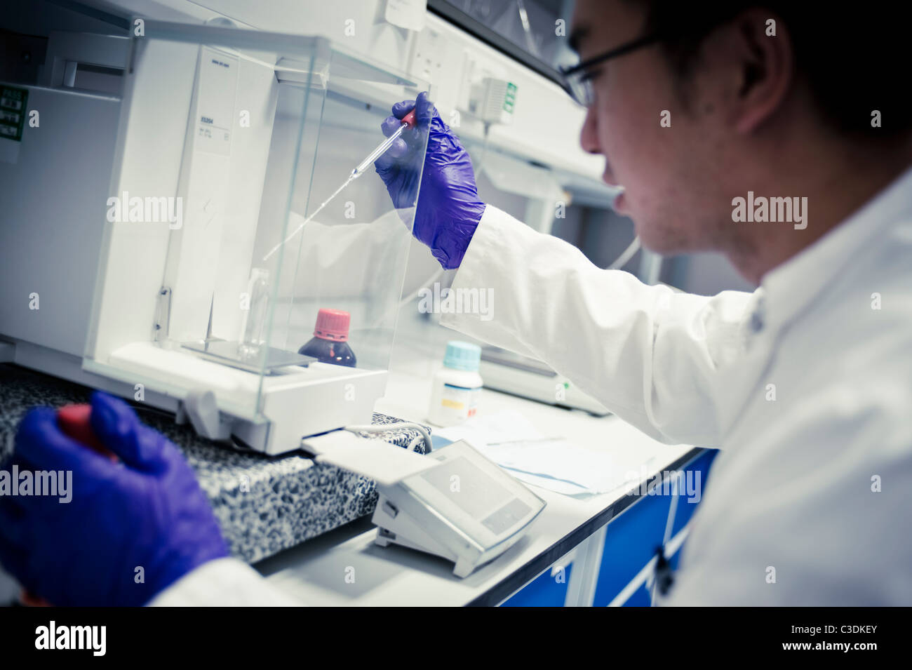 Asian male scientist in white lab coat and purple gloves with pipette in lab at scales - Stock Image