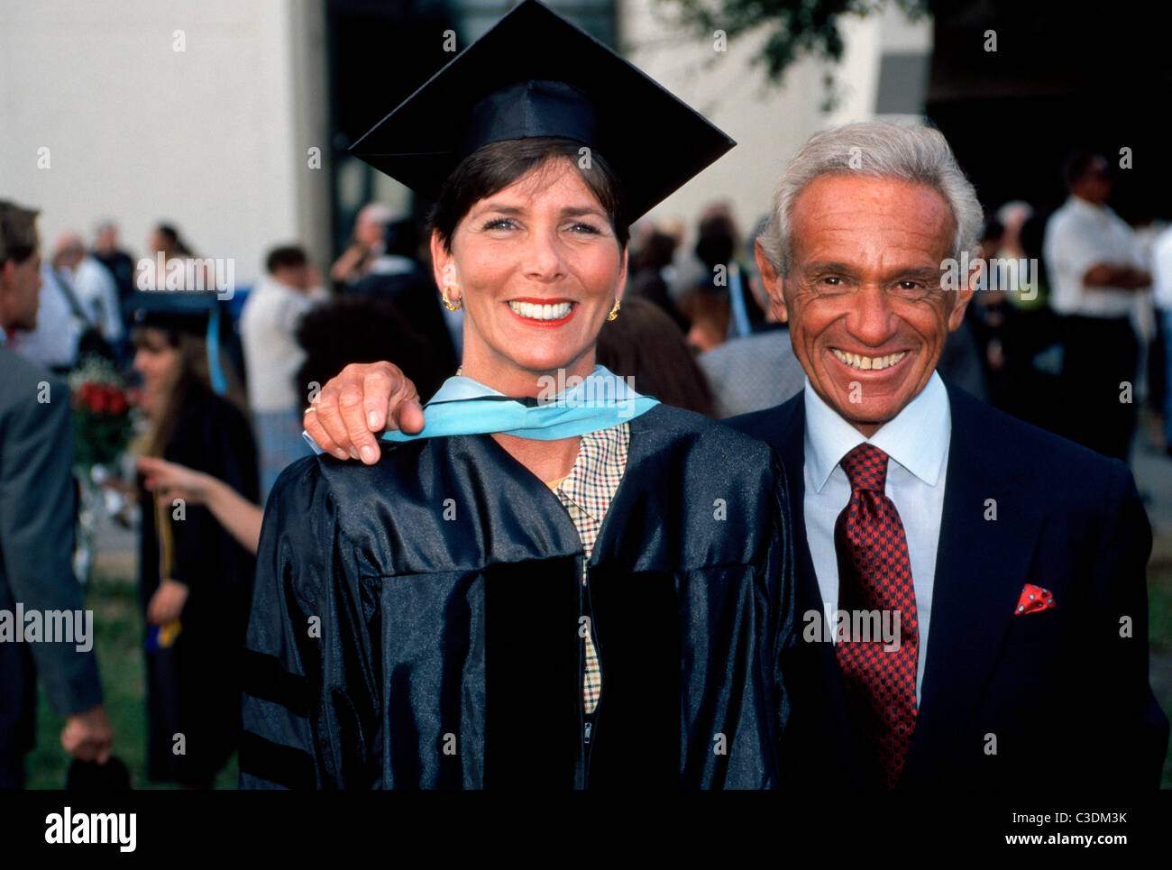 A middle-aged woman in a cap and gown poses with a relative after receiving a degree at Florida Atlantic University - Stock Image