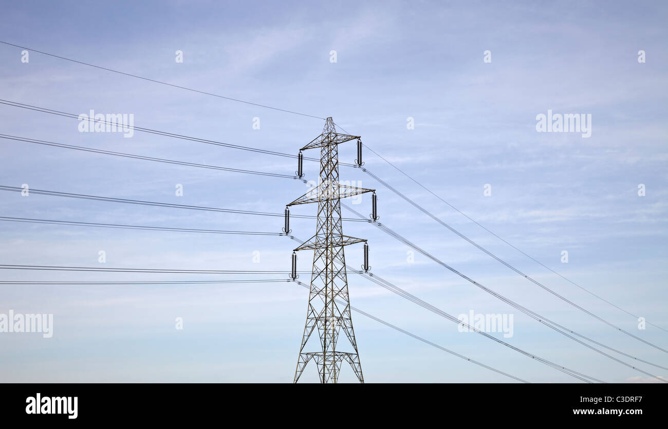 Electricity Pylon Blue sky. Large Pylon shot from distance against brilliant blue sky with cables running left and - Stock Image