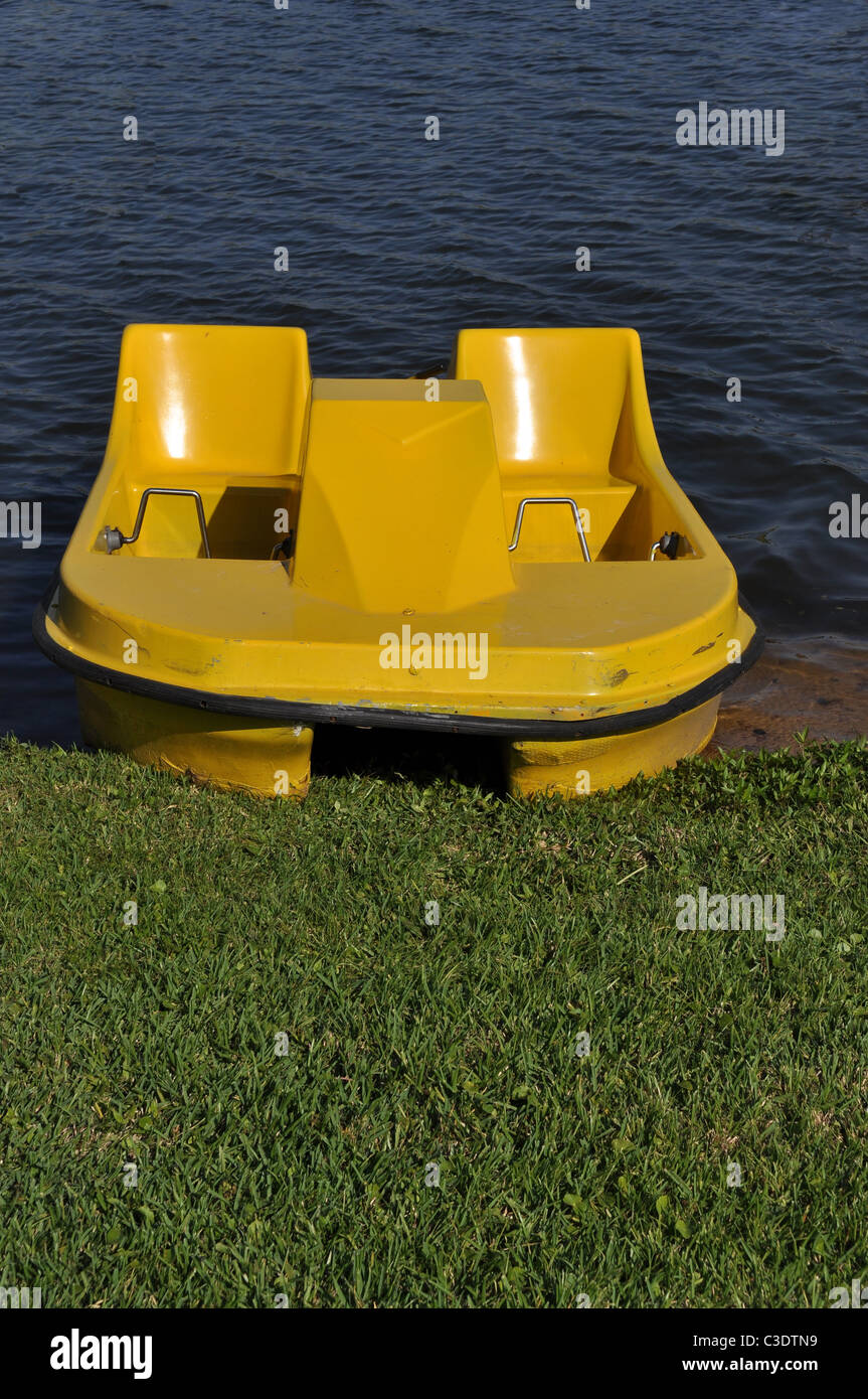 A yellow paddle boat is pulled up onto land. - Stock Image