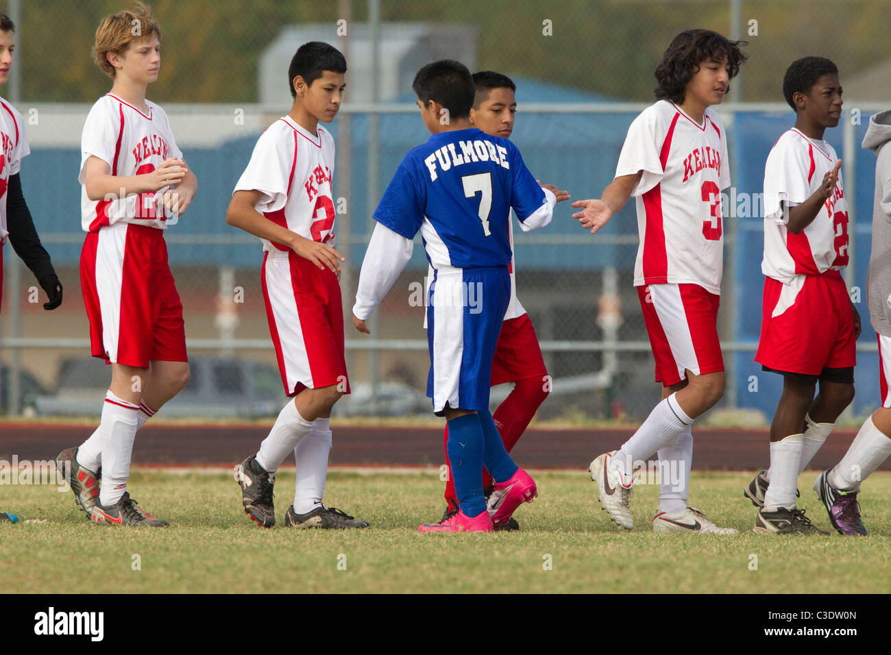 Anglo, Hispanic and African-American players from opposing teams slap hands after middle school boys' soccer - Stock Image