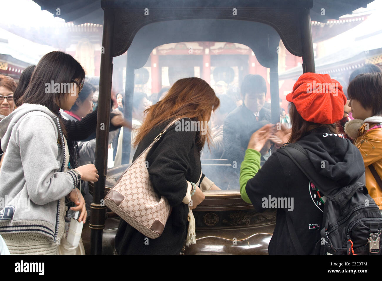 Japanese women breathing in incense smoke for good health - Stock Image