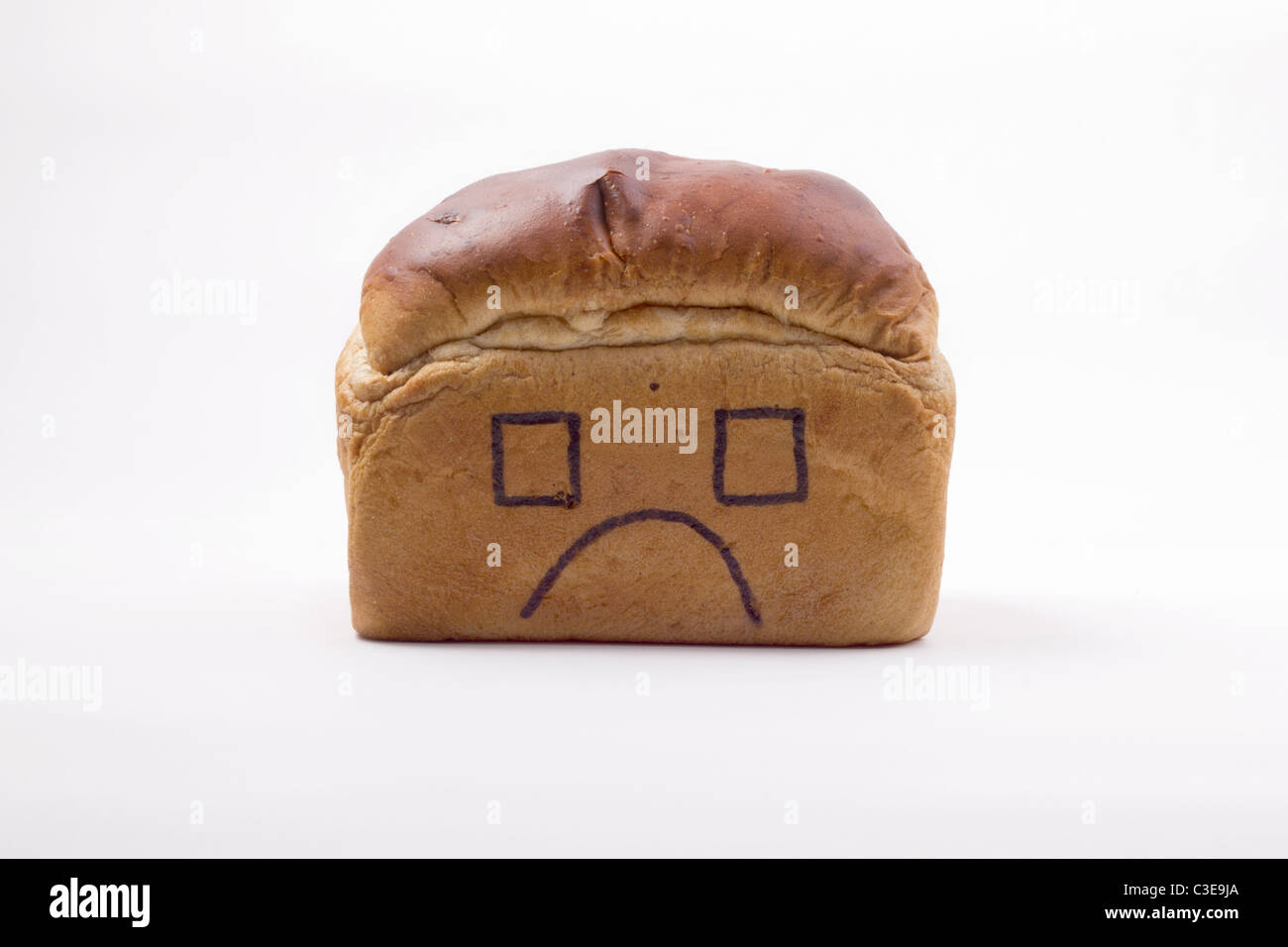 conceptual image of traditional bread with an unhappy face drawn on. Our daily bread, domestic, home life, what - Stock Image