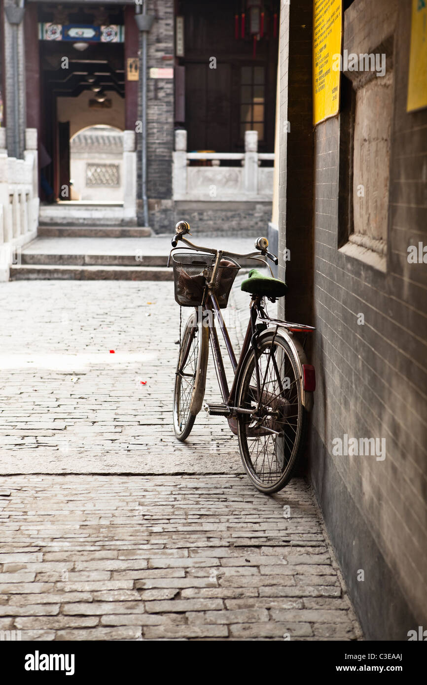 an old bicycle in an old chinese yard in a lazy sunday afternoon - Stock Image