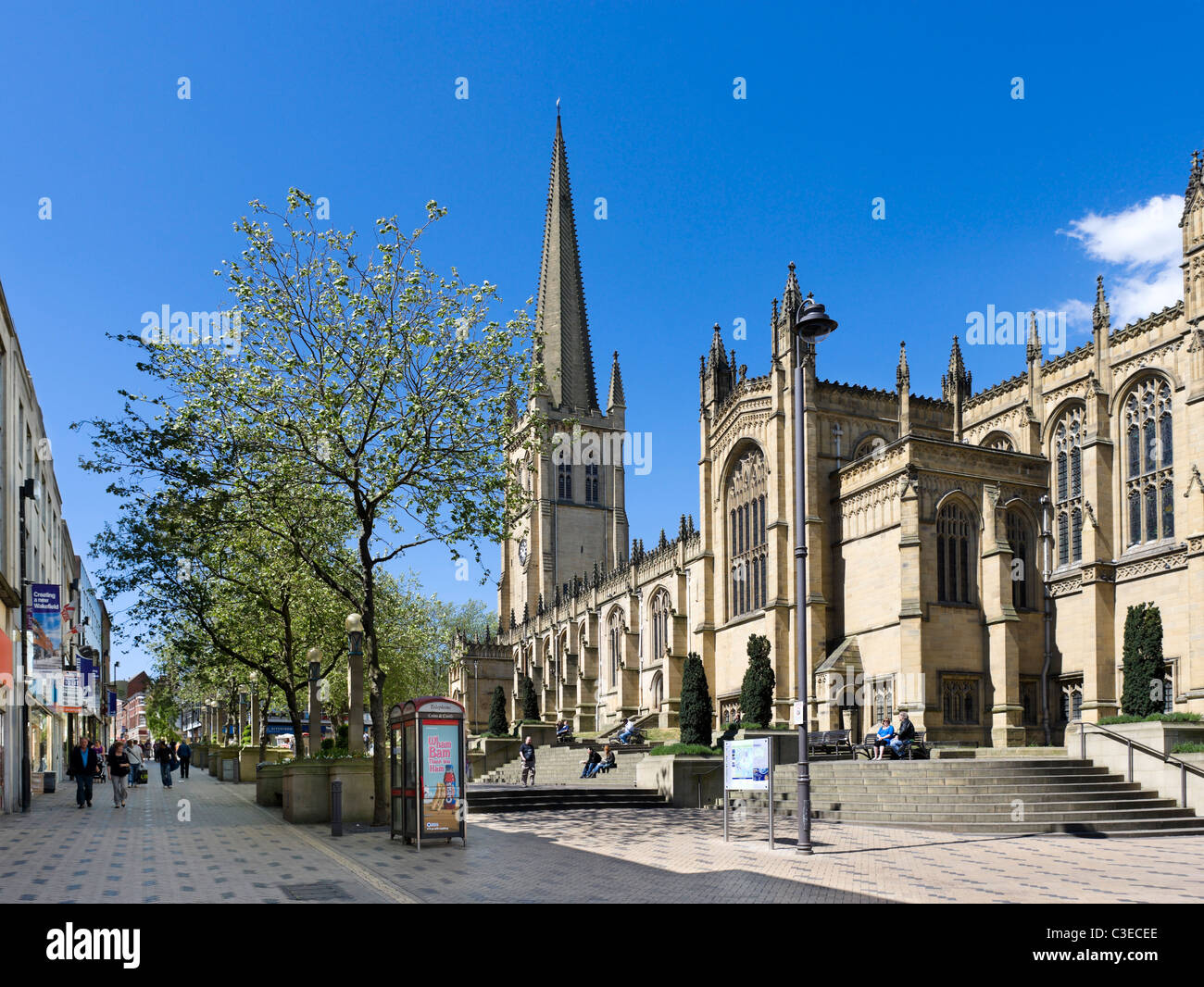 Wakefield Cathedral and shops along Kirkgate/Westgate in the city centre, Wakefield, West Yorkshire, UK - Stock Image