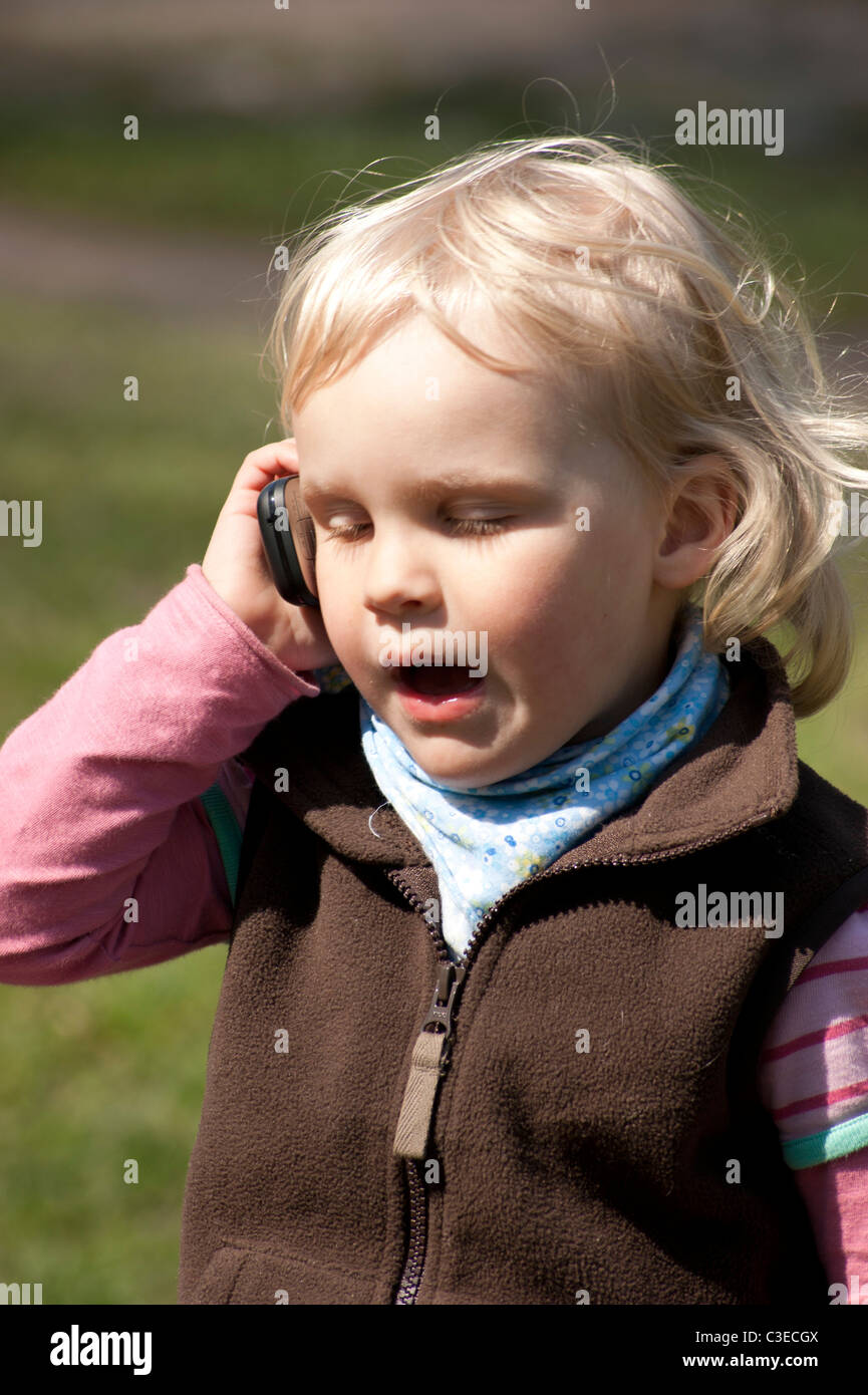 Two and half years old girl talks by phone - Stock Image