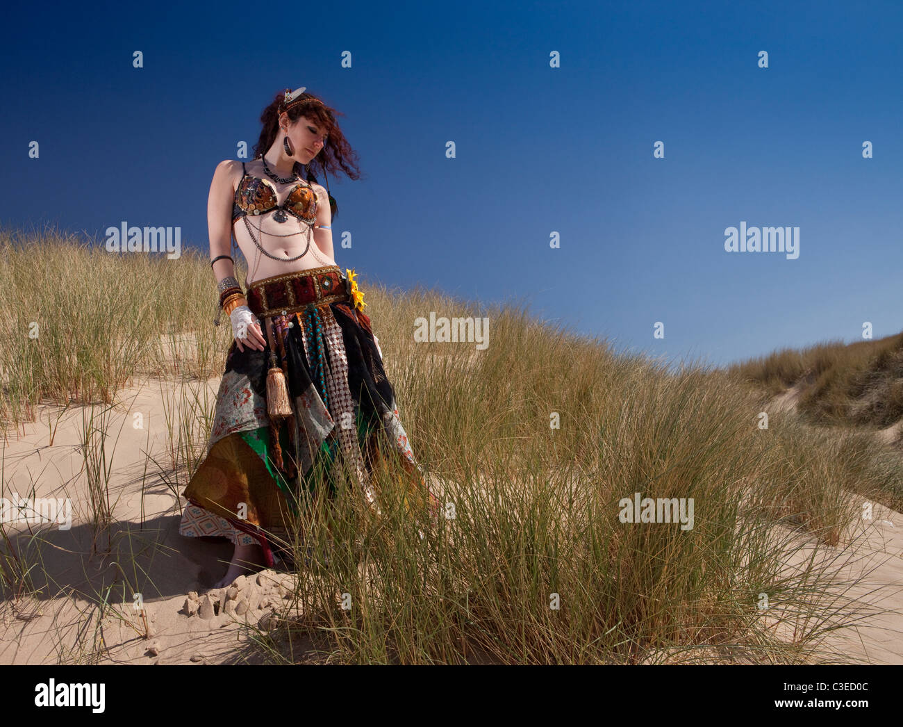 Beautiful young Tribal 'Belly Dancer' strikes pose against dramatic sky and beach in tribal clothing, UK. - Stock Image