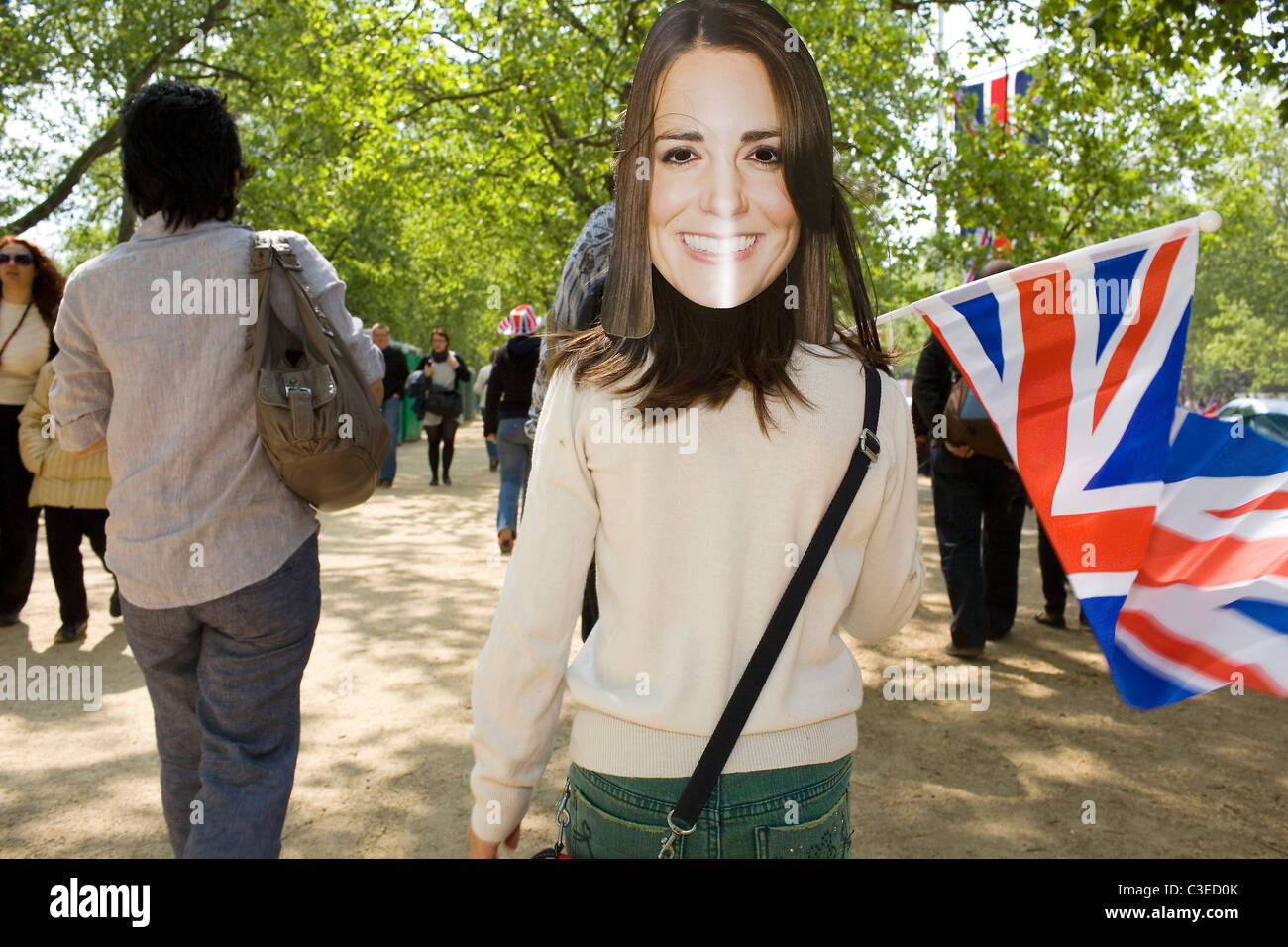 A young girl waves the union flag wearing a mask of Kate Middleton. Stock Photo