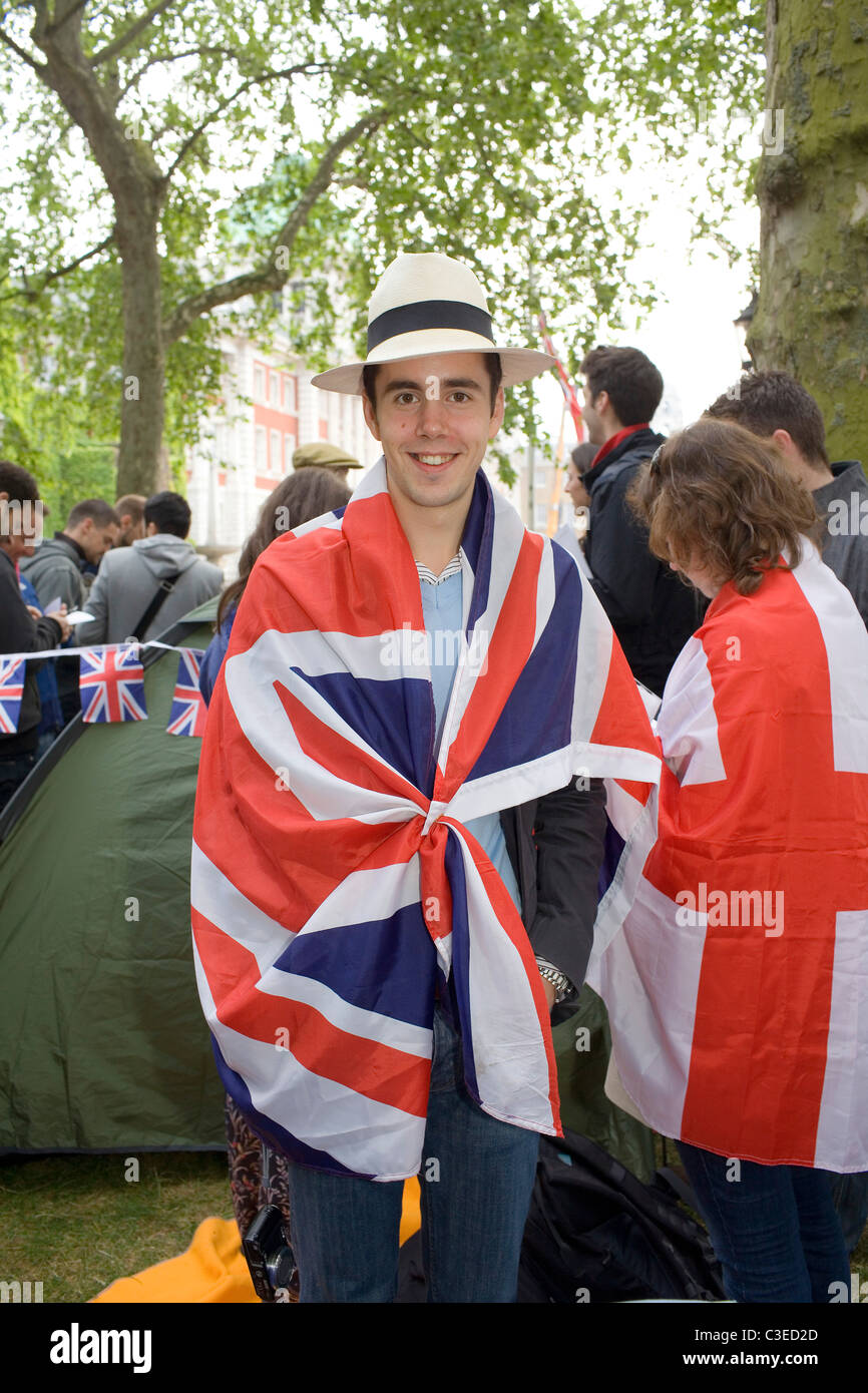 A male royal supporter wrapped in a Union Flag on the route of the royal wedding between Prince William and Kate - Stock Image